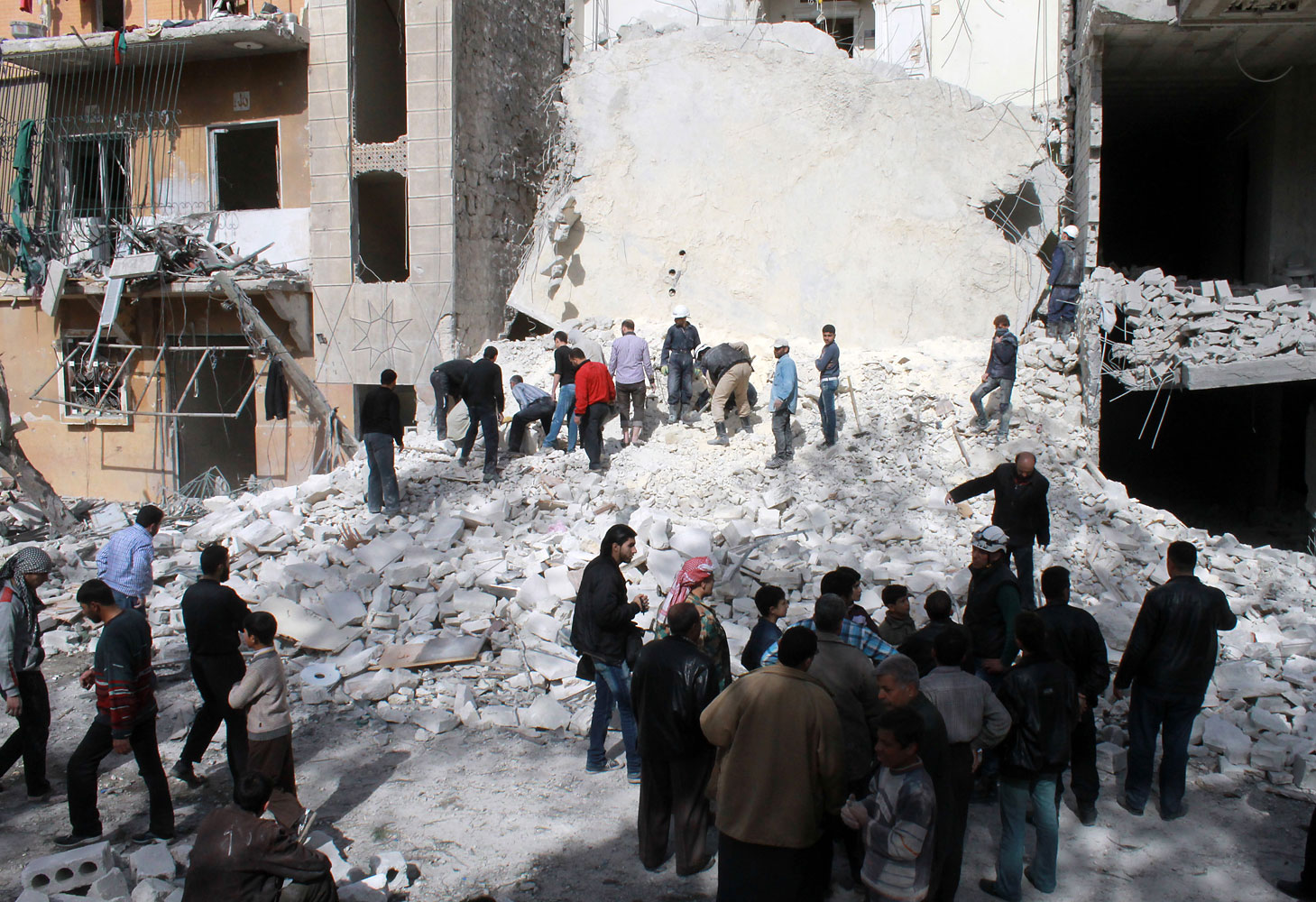 Syrians look at the destruction following an airstrike by government forces on the northern Syrian city of Aleppo on March 5, 2014.