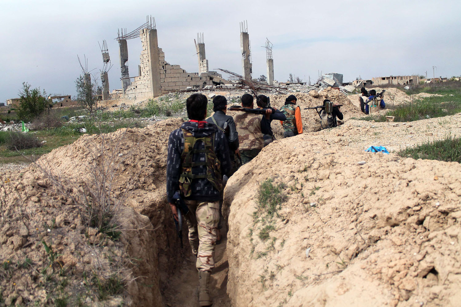 Mar. 24, 2014. Rebel fighters carry their weapons as they walk along a trench in the northeastern city of Deir Ezzor. Fighting with pro-regime fighters continues as more than 146,000 people have died in the three-years and millions more have been displaced.