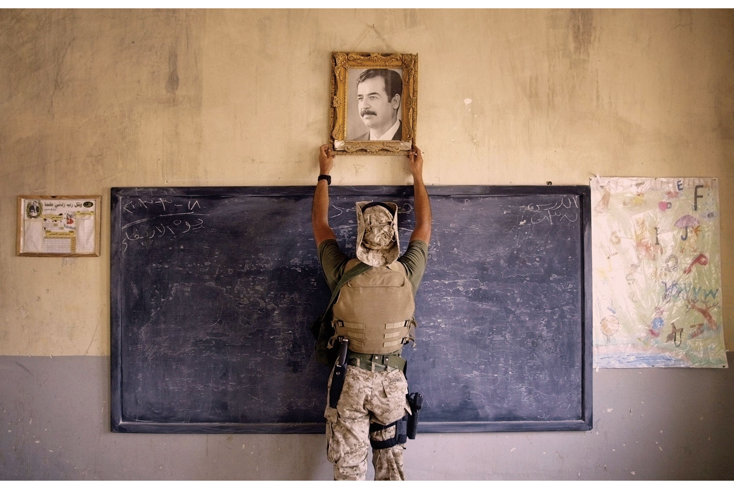 From Chris Hondros' Testament, A U.S. Marine pulls down a picture of Saddam Hussein at a school in Al-Kut, Iraq.