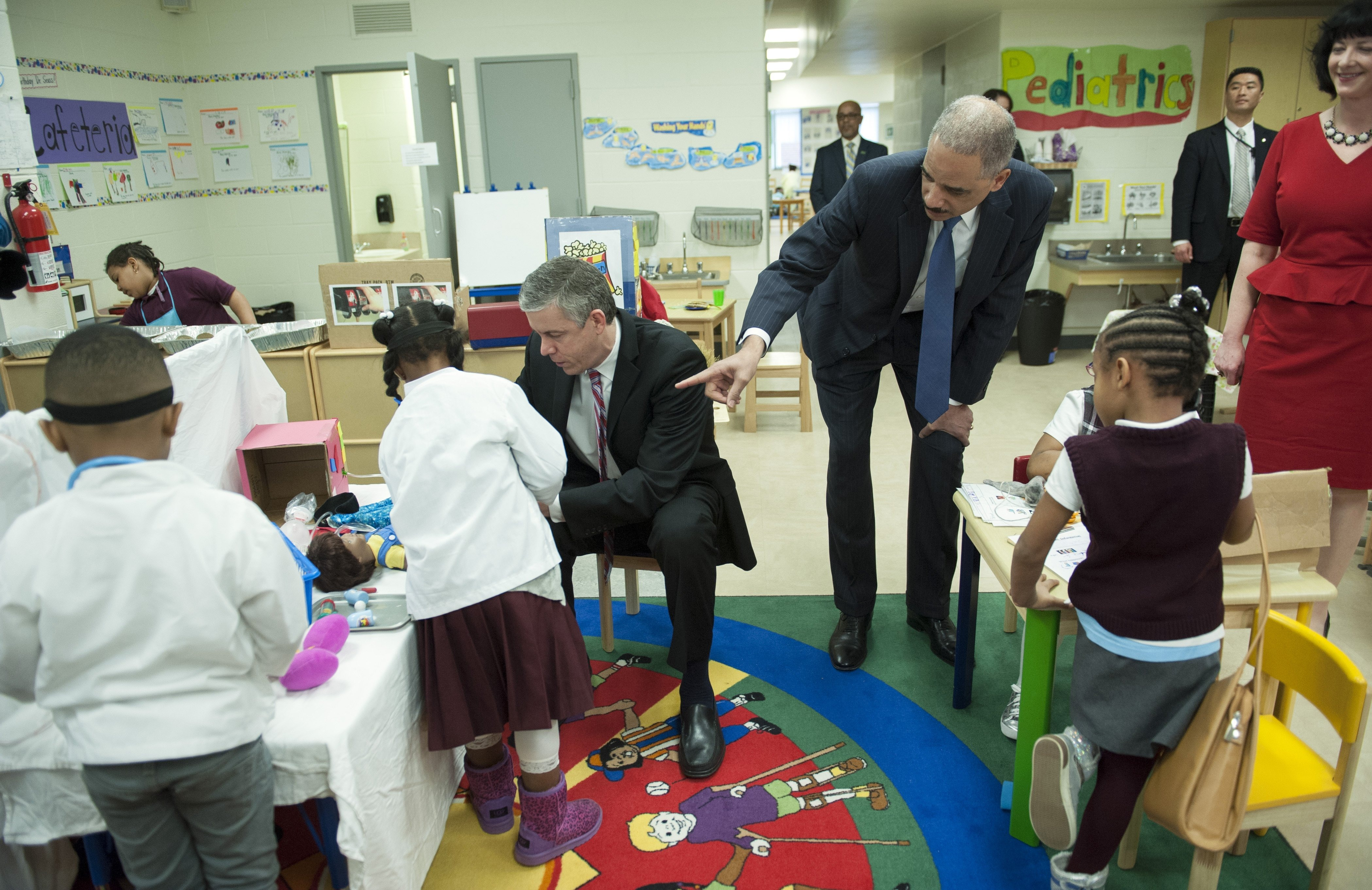 Education Secretary Arne Duncan and Attorney General Eric Holder meet with a preschool class prior to participating in a discussion on the importance of universal access to preschool at J. Ormond Wilson Elementary School in Washington, March 21, 2014.