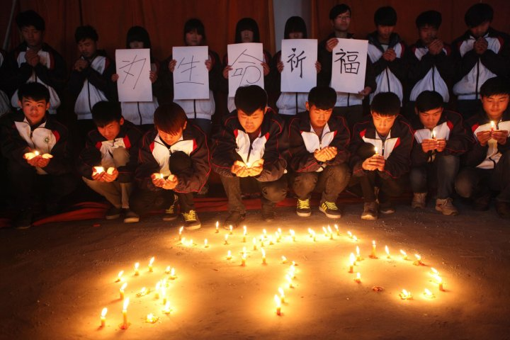 High school students in Lianyungang in China's eastern Jiangsu province hold a vigil for the passengers and crew of Flight MH 370