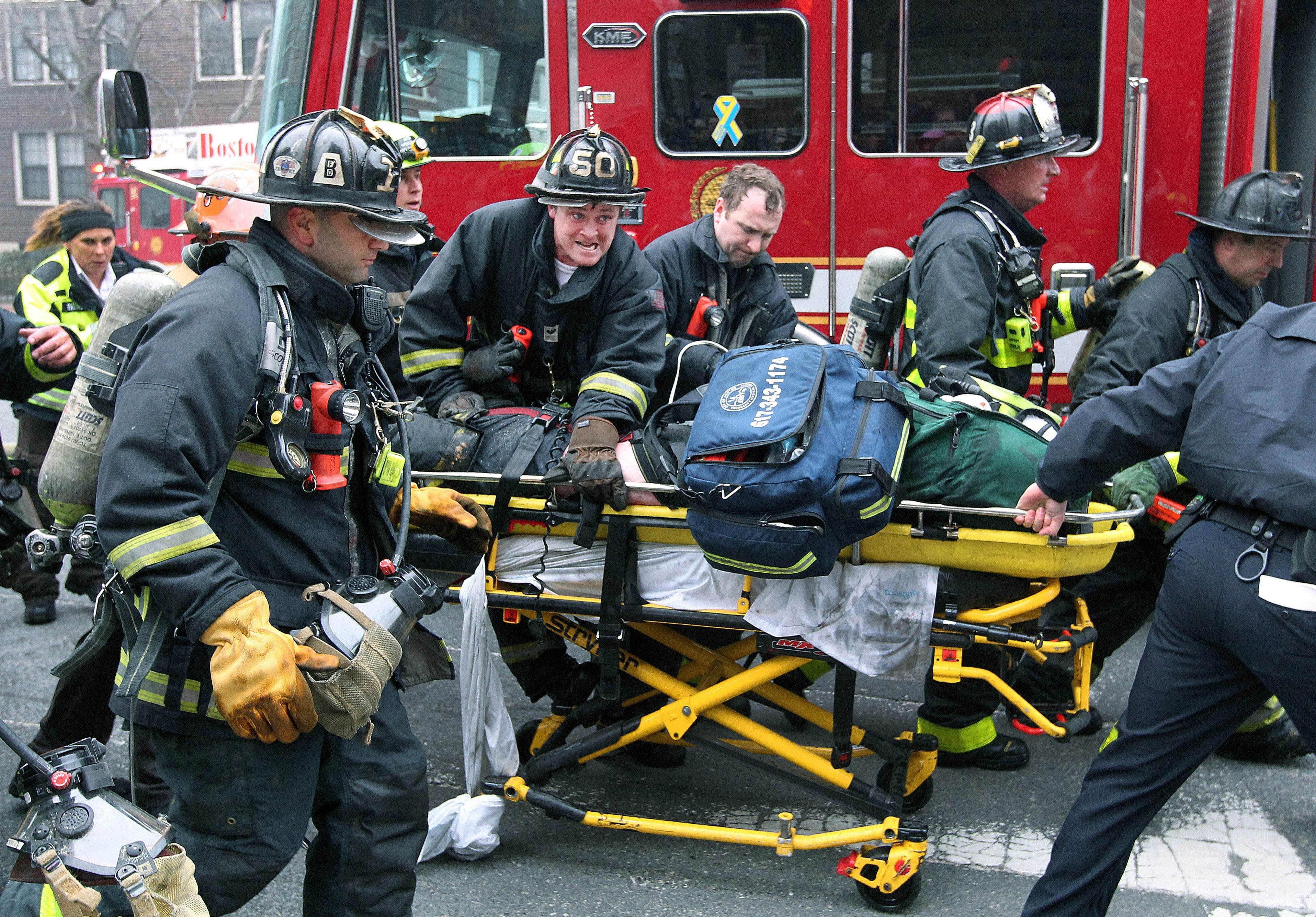 Boston Fire Department firefighters working on a fellow firefighter as he is rushed to an ambulance after being injured during a nine alarm fire in the Back Bay neighborhood of Boston, March 26, 2014.