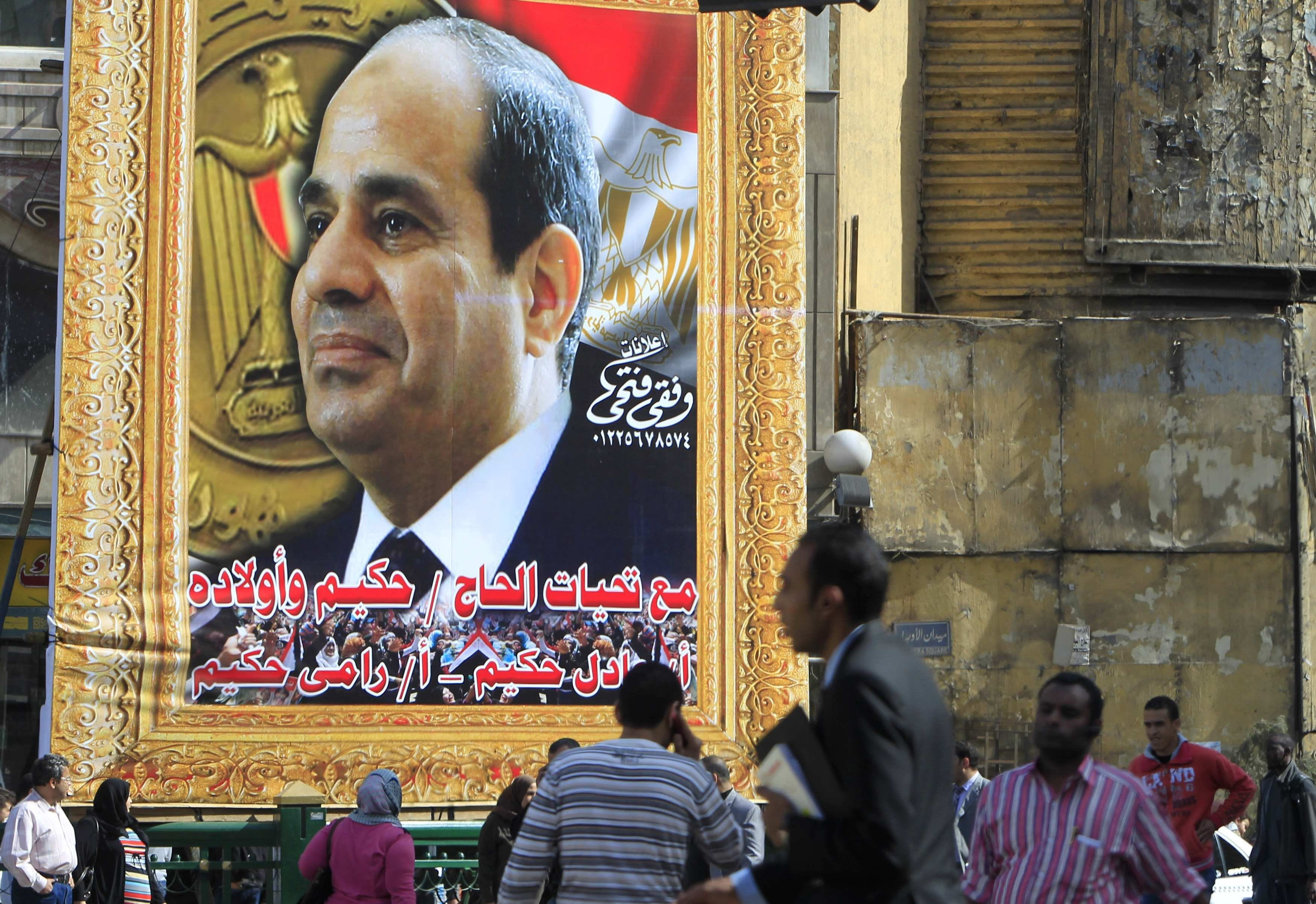 People walk past a banner for Egypt's army chief Field Marshal Abdel Fattah al-Sisi in downtown Cairo March 26, 2014.