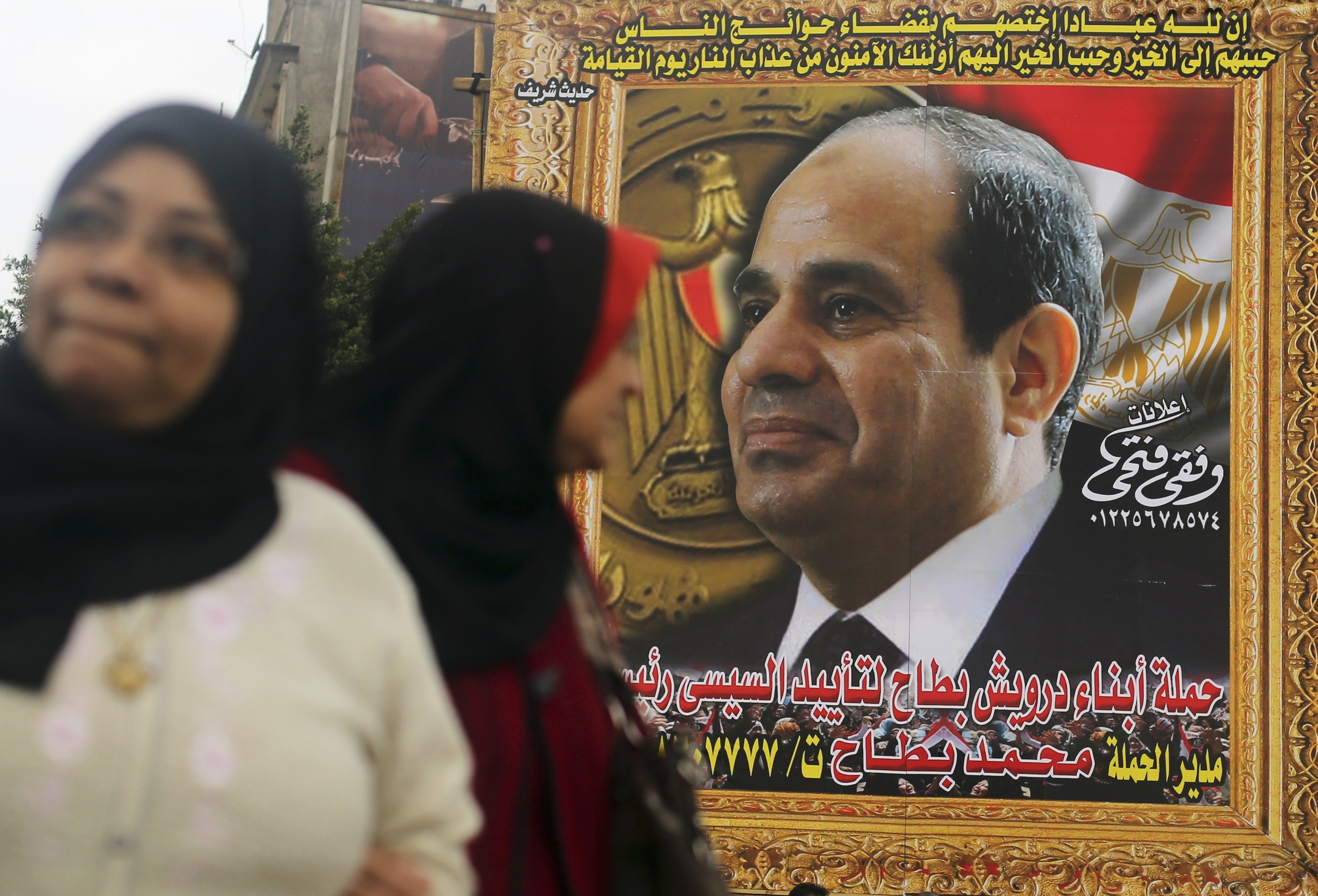 Women walk in front of a huge banner for Egypt's army chief, Field Marshal Abdel Fattah al-Sisi in downtown Cairo, March 13, 2014.