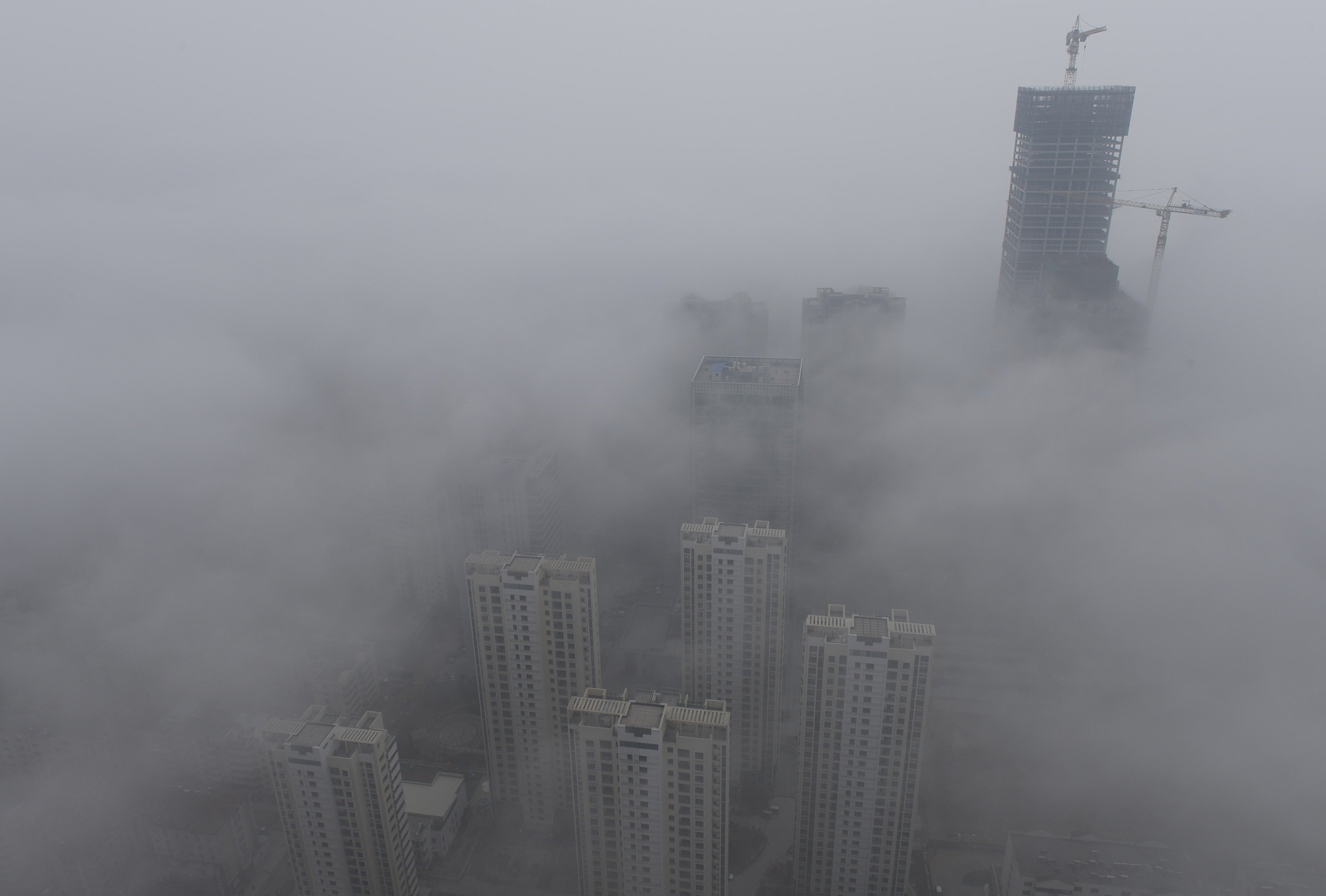 Buildings are seen shrouded in heavy haze at Qingdao development zone, Shandong province, February 25, 2014.