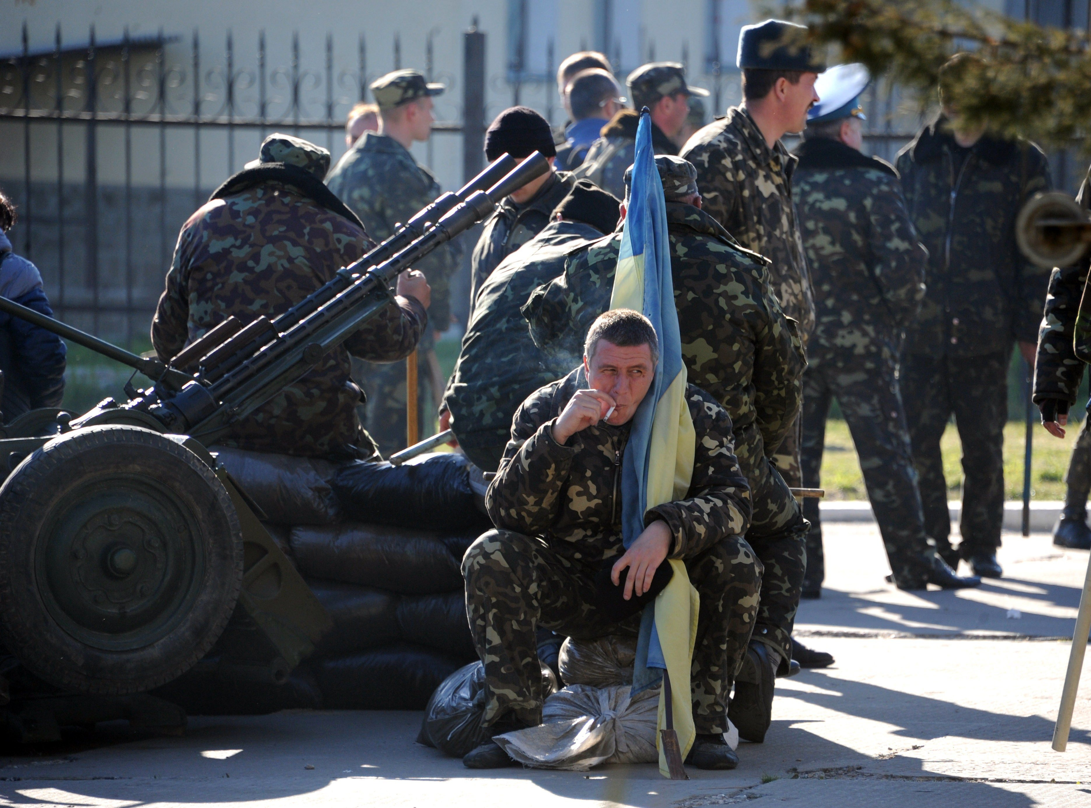 A Ukrainian officer holds his flag as he smokes a cigarette before pro-Russia militia and Russian armed forces backed by armoured vehicles broke inside the Ukrainian airbase in the small city of Belbek near the Crimean city of Sevastopol on March 22, 2014.
