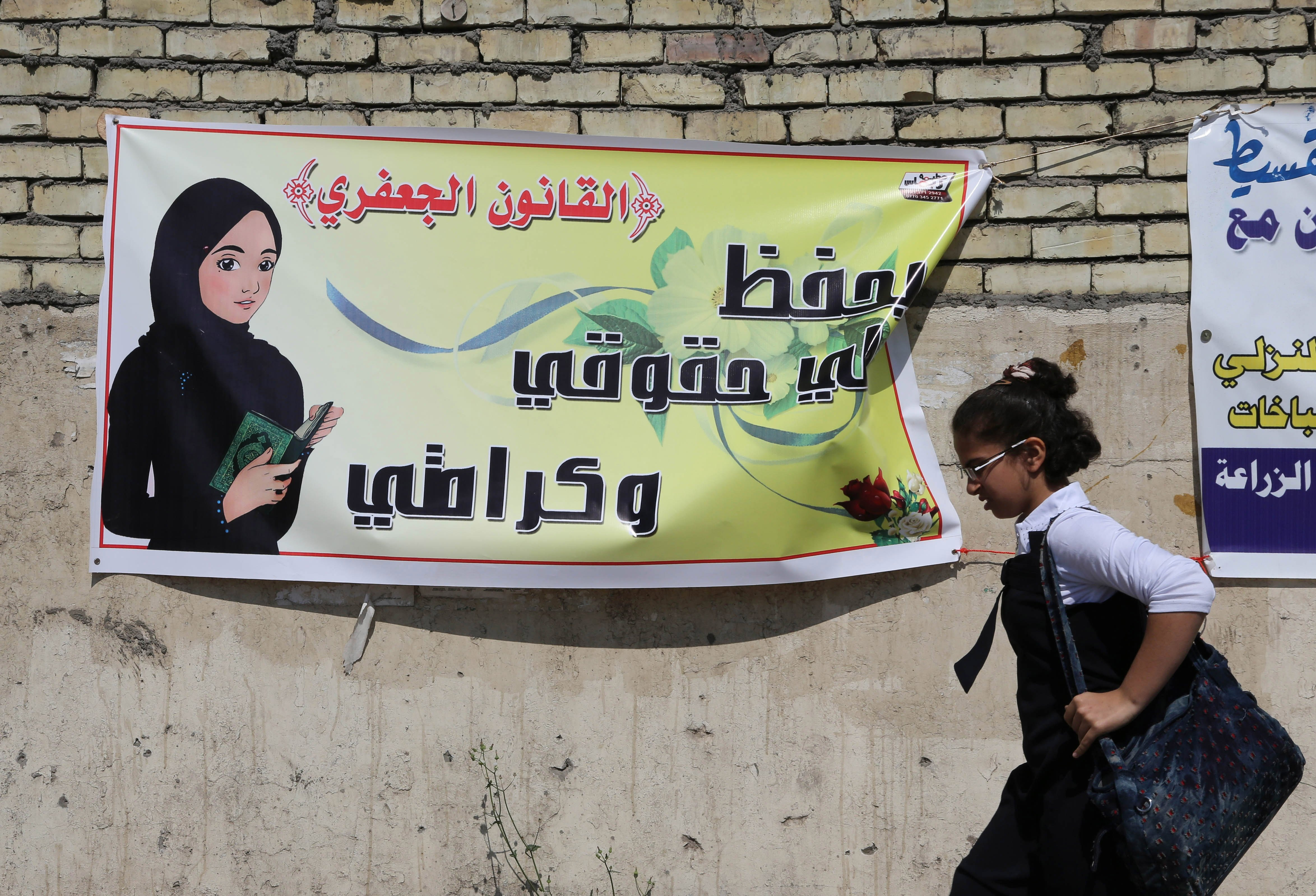 A schoolgirl passes by a banner that reads,  the Jaafari Personal Status Law saves my rights and my dignity,  in Baghdad, March 13, 2014.
