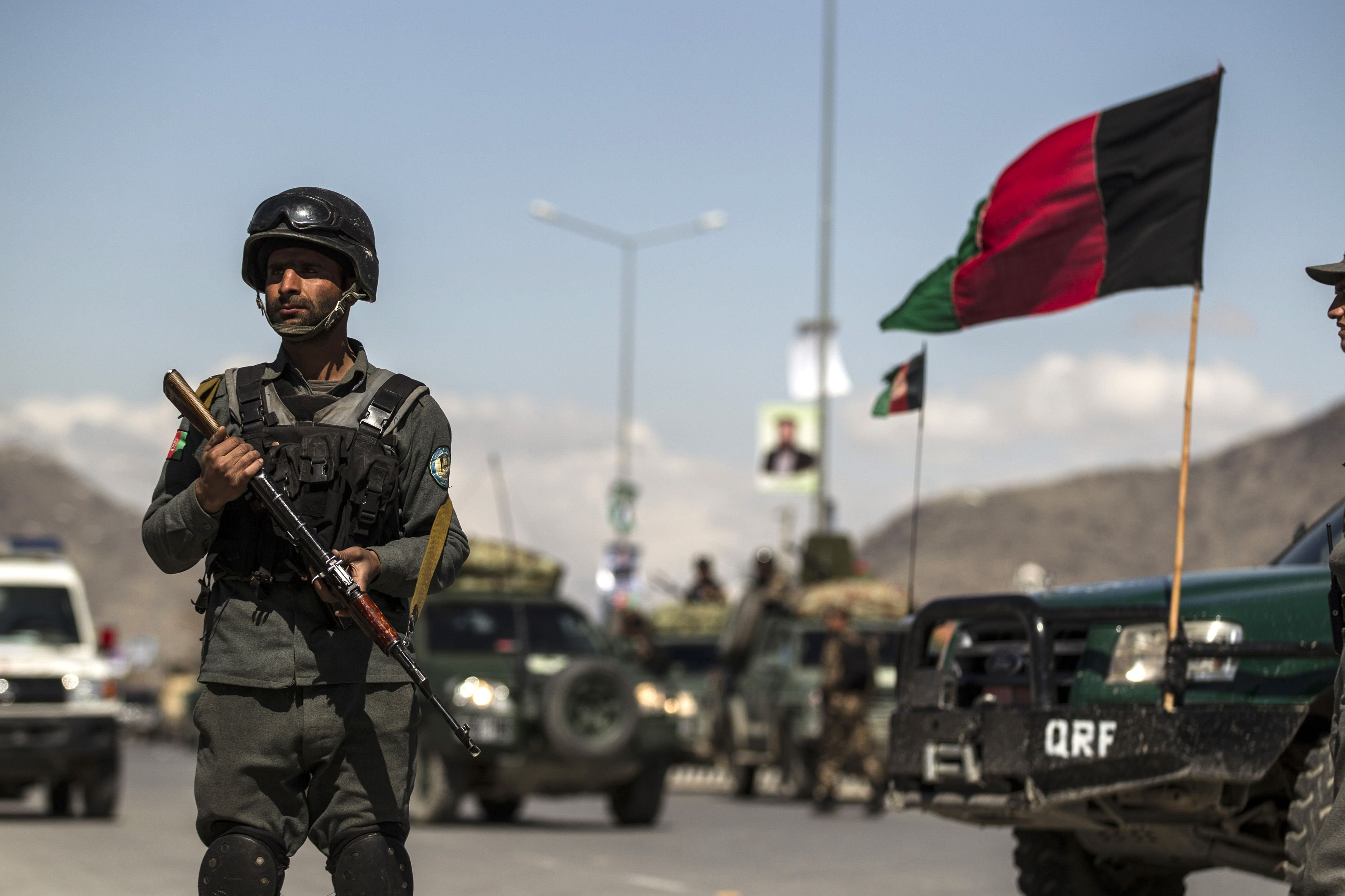 An Afghan policeman stands guard near the site of an attack in Kabul, March 25, 2014.