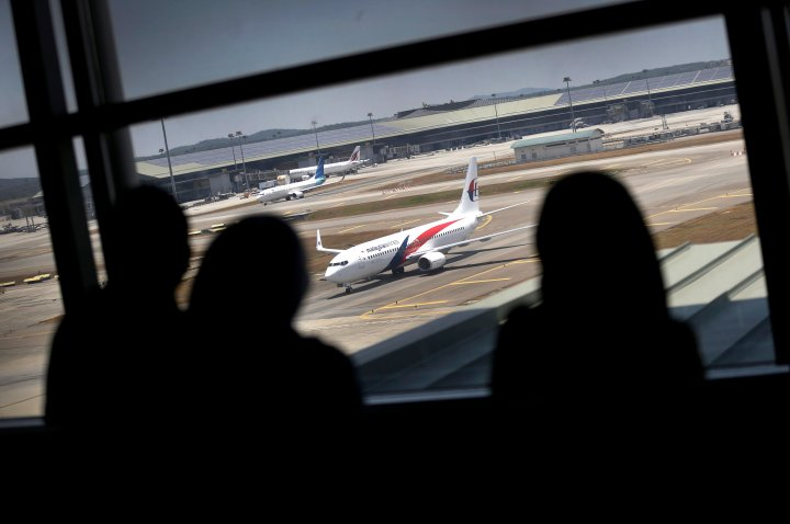 Women are silhouetted as they watch a Malaysia Airlines jet taxi on the tarmac at the Kuala Lumpur International Airport.