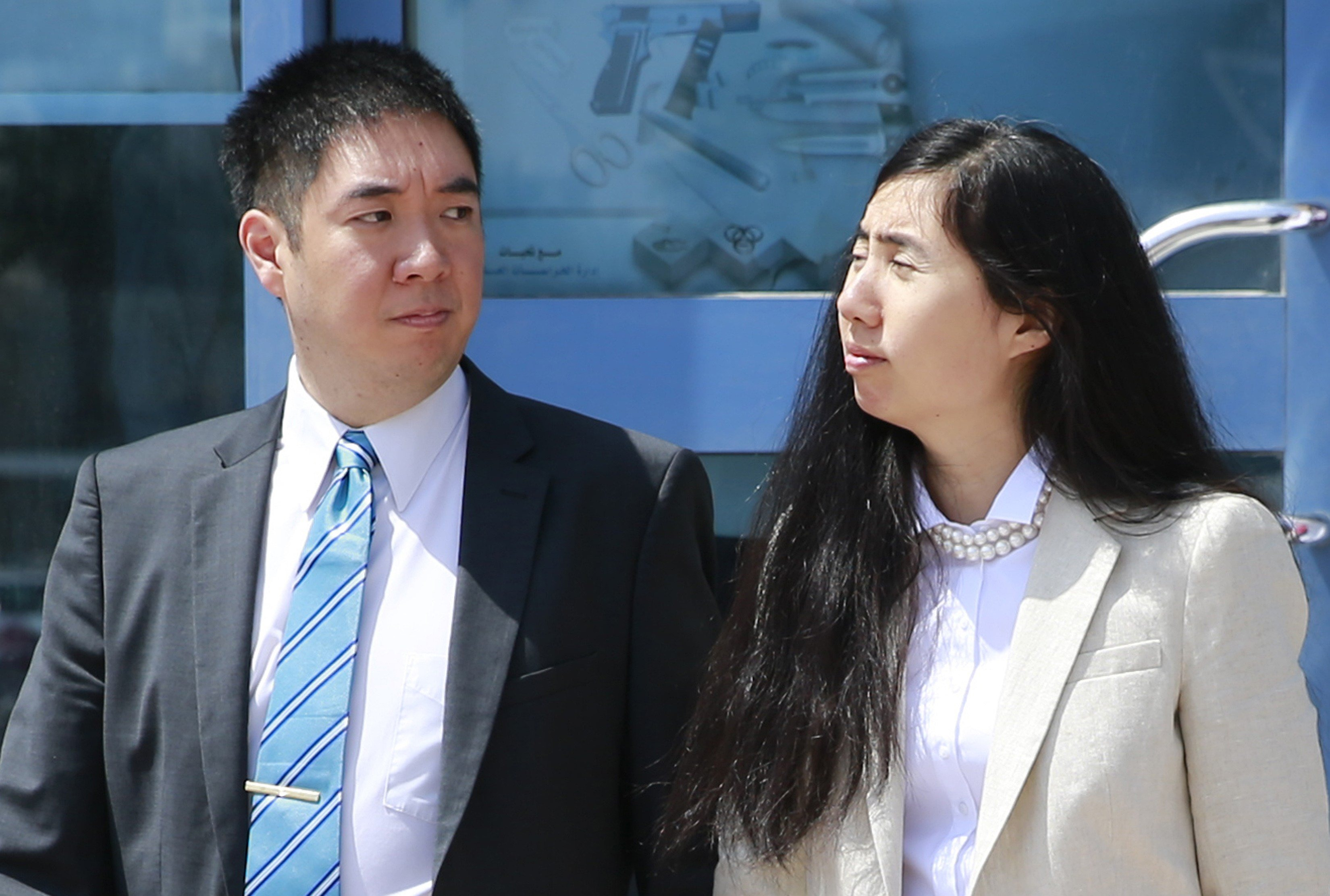 Matthew and Grace Huang, an American couple charged with starving their 8-year-old adopted daughter to death, stand outside the entrance of the Court of First Instance after their trial in Doha, March 27, 2014.