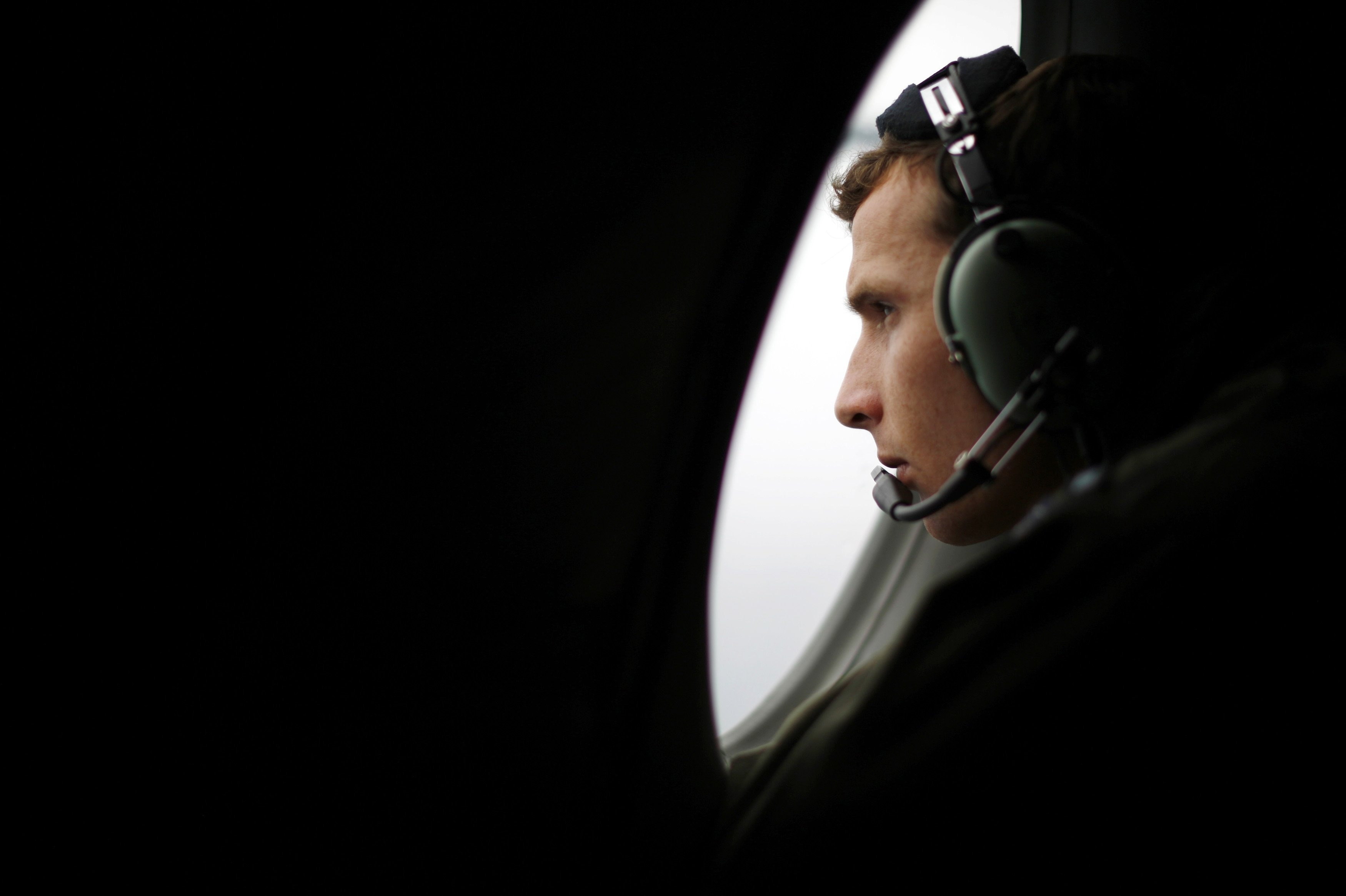 A crew member aboard a Royal New Zealand Air Force P-3K2 Orion aircraft searches for the missing Malaysian Airlines Flight MH370 over the southern Indian Ocean on March 22, 2014