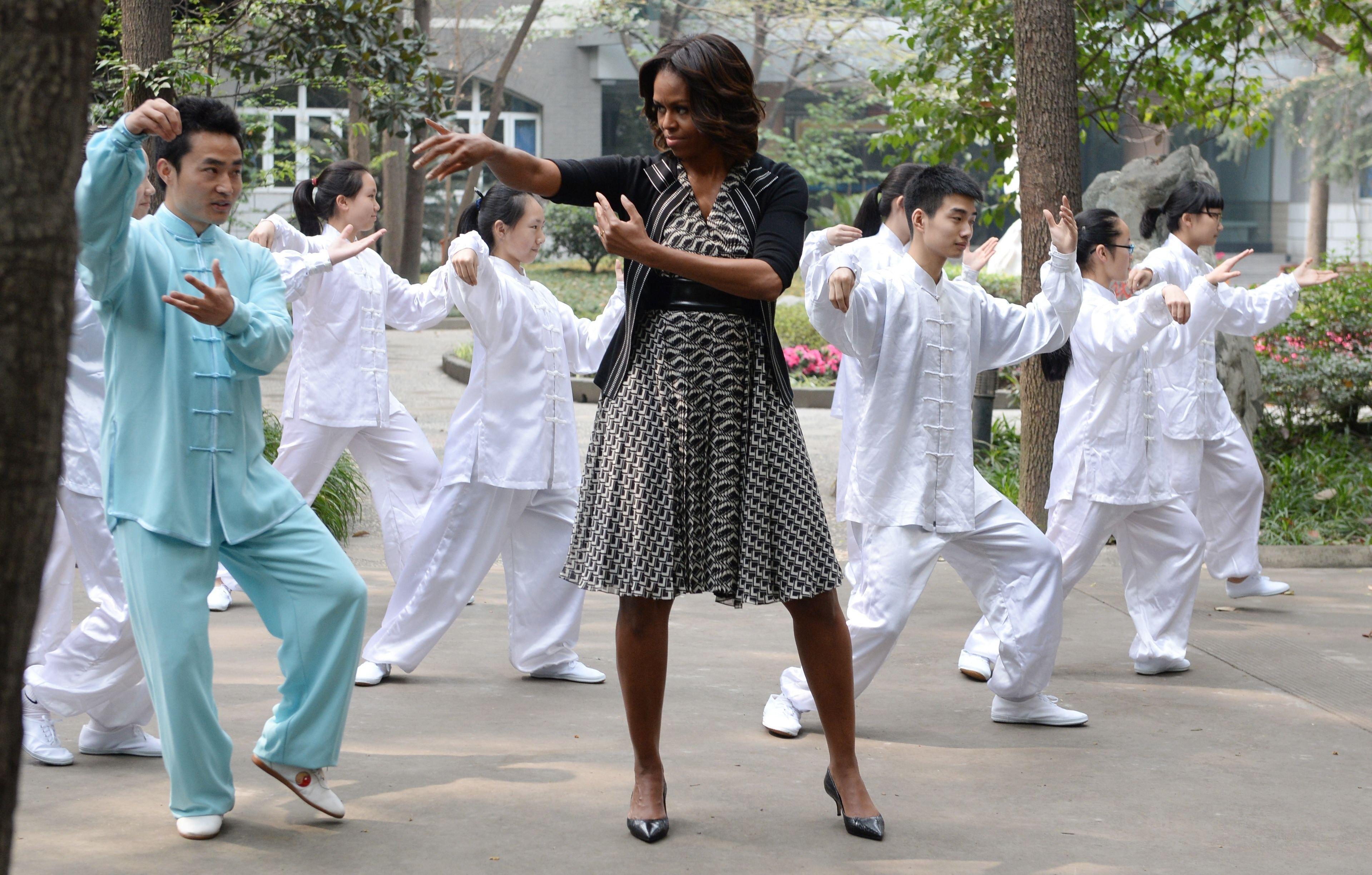 US First Lady Michelle Obama performs  tai chi  with students from the Chengdu No7 High School in Chengdu in China's southwest Sichuan province on March 25, 2014.