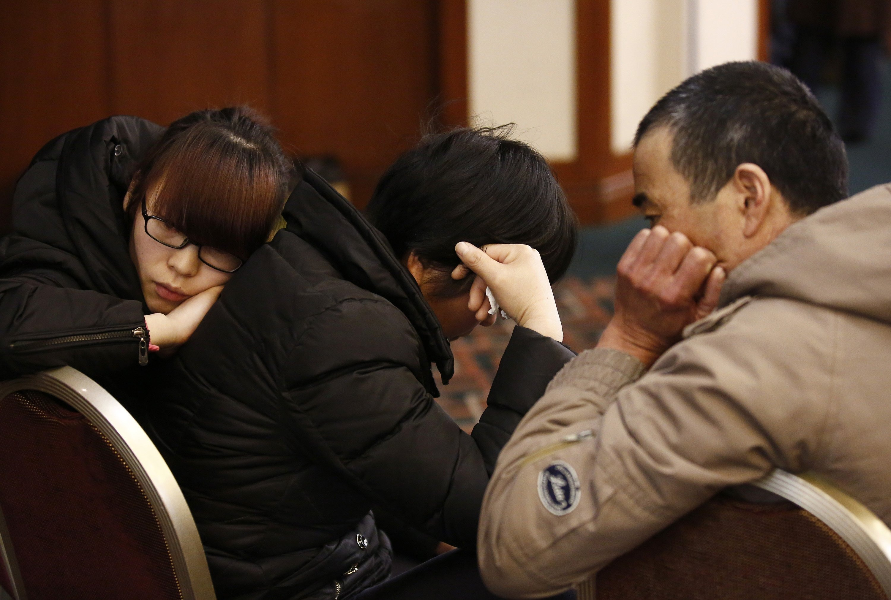 Family members of a passenger onboard the missing Malaysia Airlines Flight 370 react as they listen to a briefing from the airline company at a hotel in Beijing on March 18, 2014