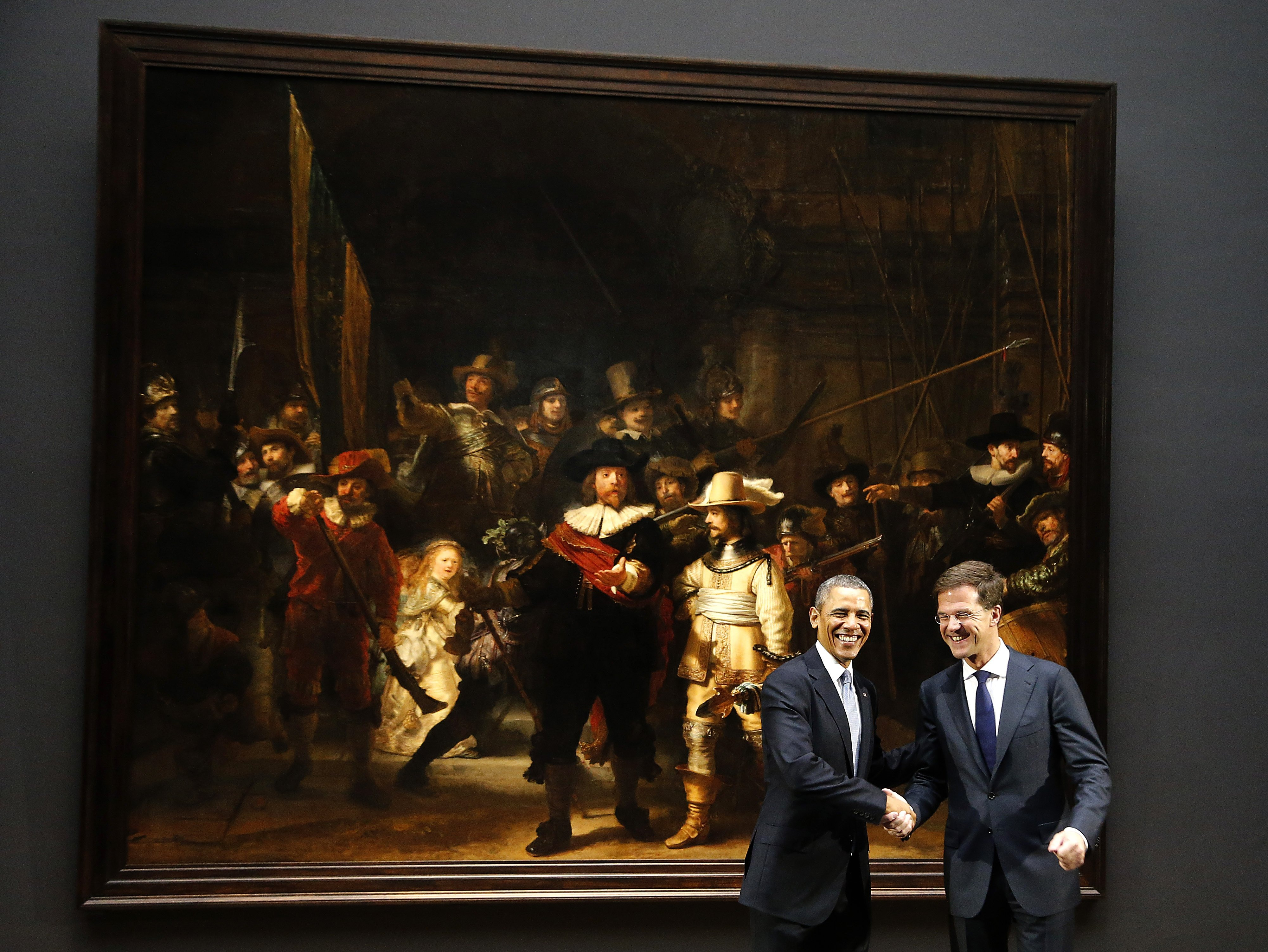 U.S. President Barack Obama, left, shakes hands with Dutch Prime Minister Mark Rutte, right, in front of  Dutch master Rembrandt's The Night Watch painting during a visit to the Rijksmuseum in Amsterdam, Netherlands, on Monday, March 24, 2014.