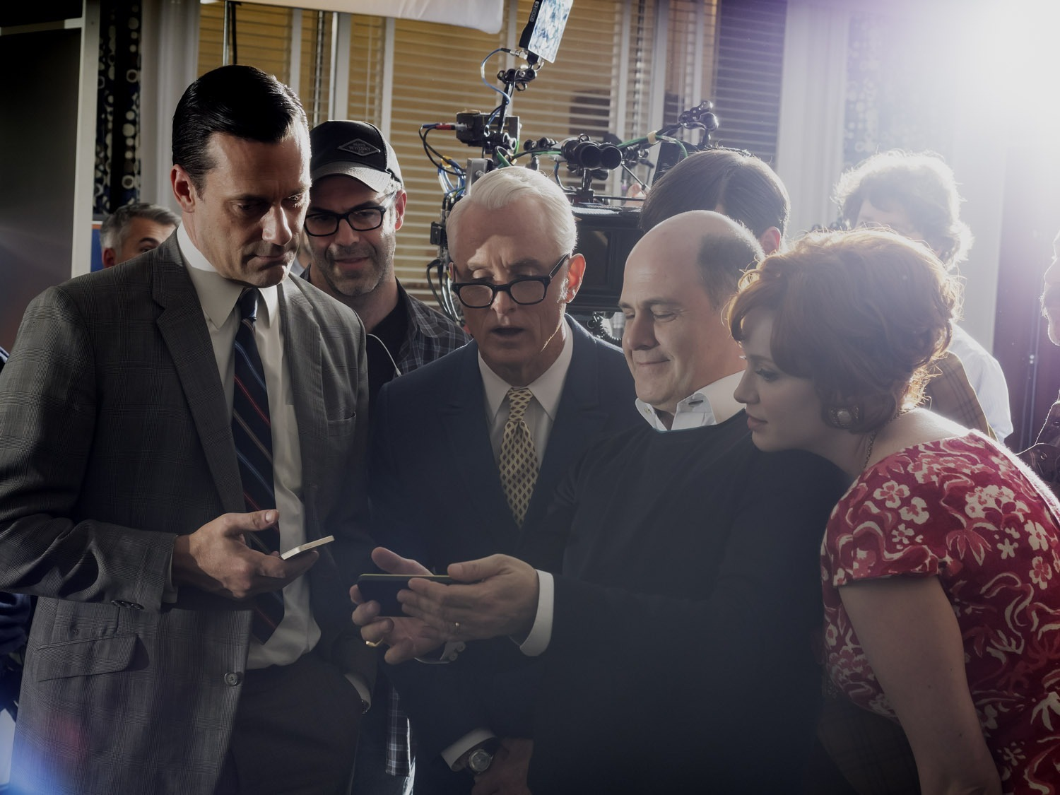 While on the Los Angeles set of Mad Men for the April 7 cover shoot, photographer Alex Majoli found that the theatricality of a TV set—above, Jon Hamm, John Slattery, Matthew Weiner and Christina Hendricks check out a phone pic—was something he recognized from working in other settings.  In conflict zones, hospitals, cities, I found a sort of theater in it,  he explains.  The moment you are there with a camera, everyone has a role, me included. So photographing actors on a Hollywood set was like a present for me, searching for those theatrical scenes.