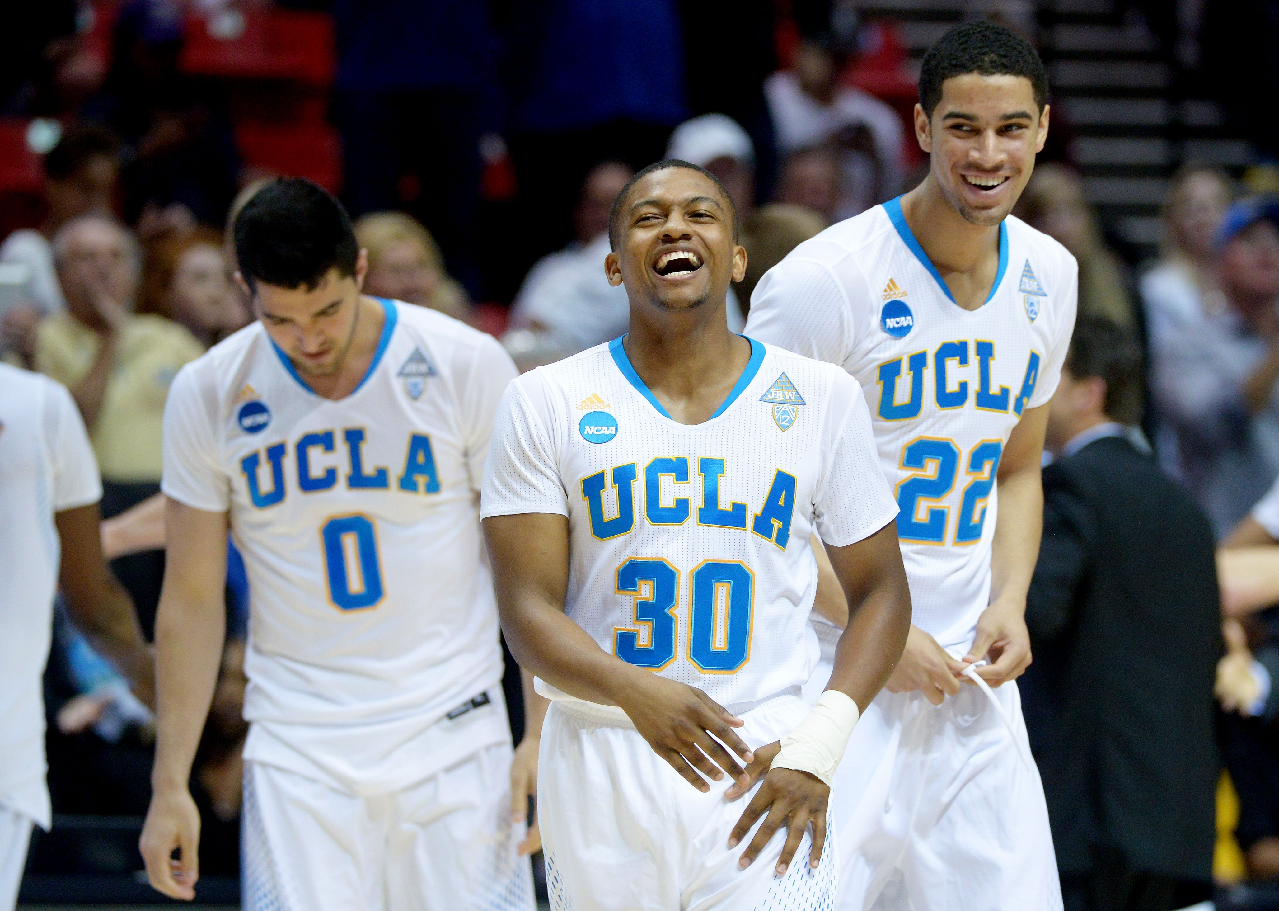 From left: Nick Kazemi, Aubrey Williams and Noah Allen of the UCLA Bruins celebrate their 77 to 60 win over the Stephen F. Austin Lumberjacks during the third round of the 2014 NCAA Tournament on March 23, 2014.