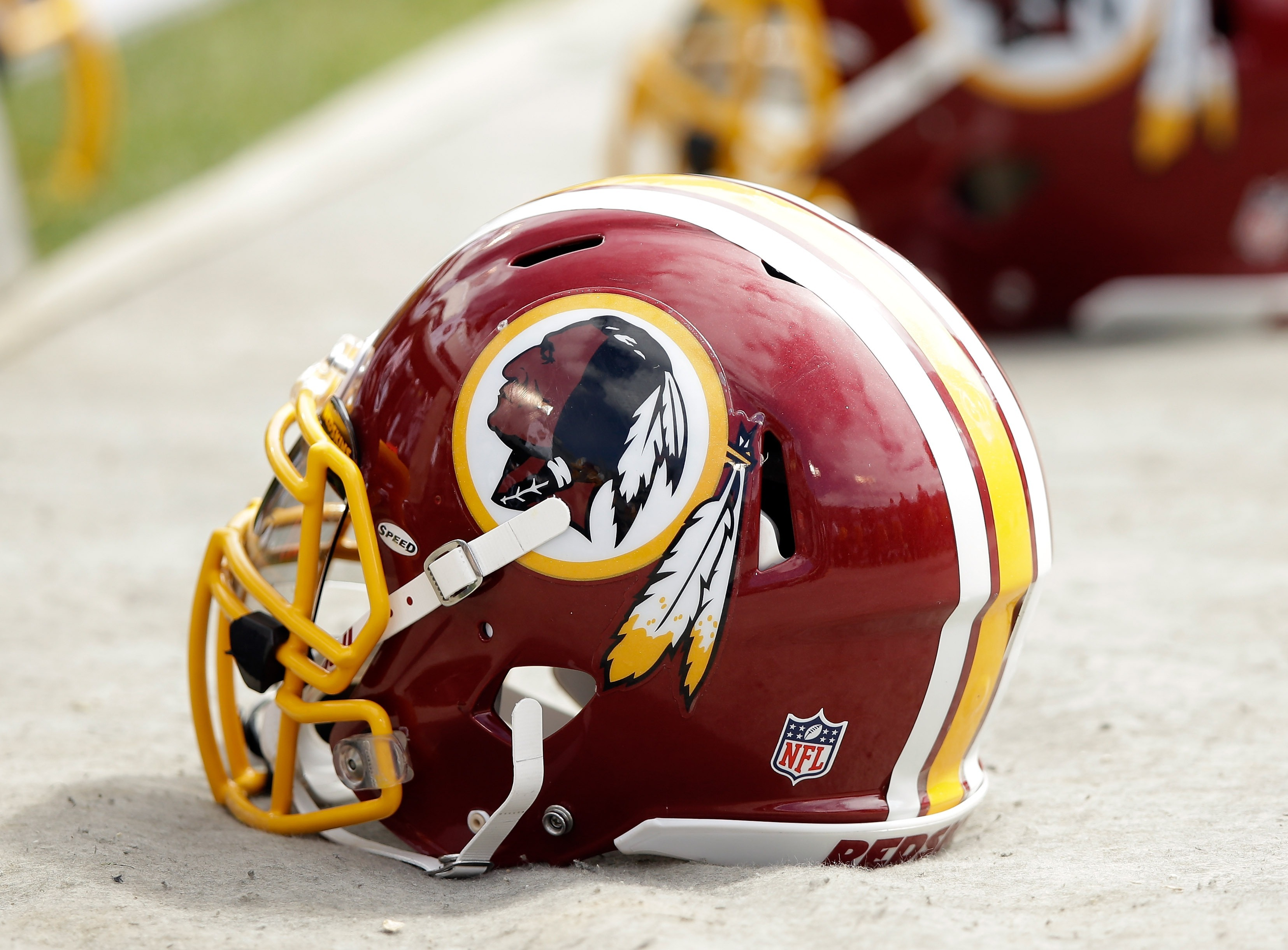 Washington Redskins helmets lay on the ground during a game against the Oakland Raiders