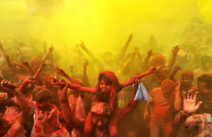 Indian revellers cover each other with coloured powder and dance while taking part in Holi festival celebrations in Guwahati on March 17, 2014.