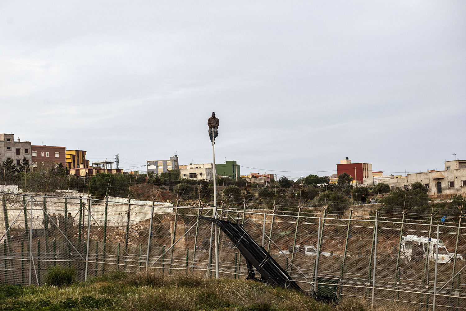 A would-be immigrant waits sitted on a mast on the other side of fences near Beni Enza, into the north African Spanish enclave of Melilla on March 28, 2014.