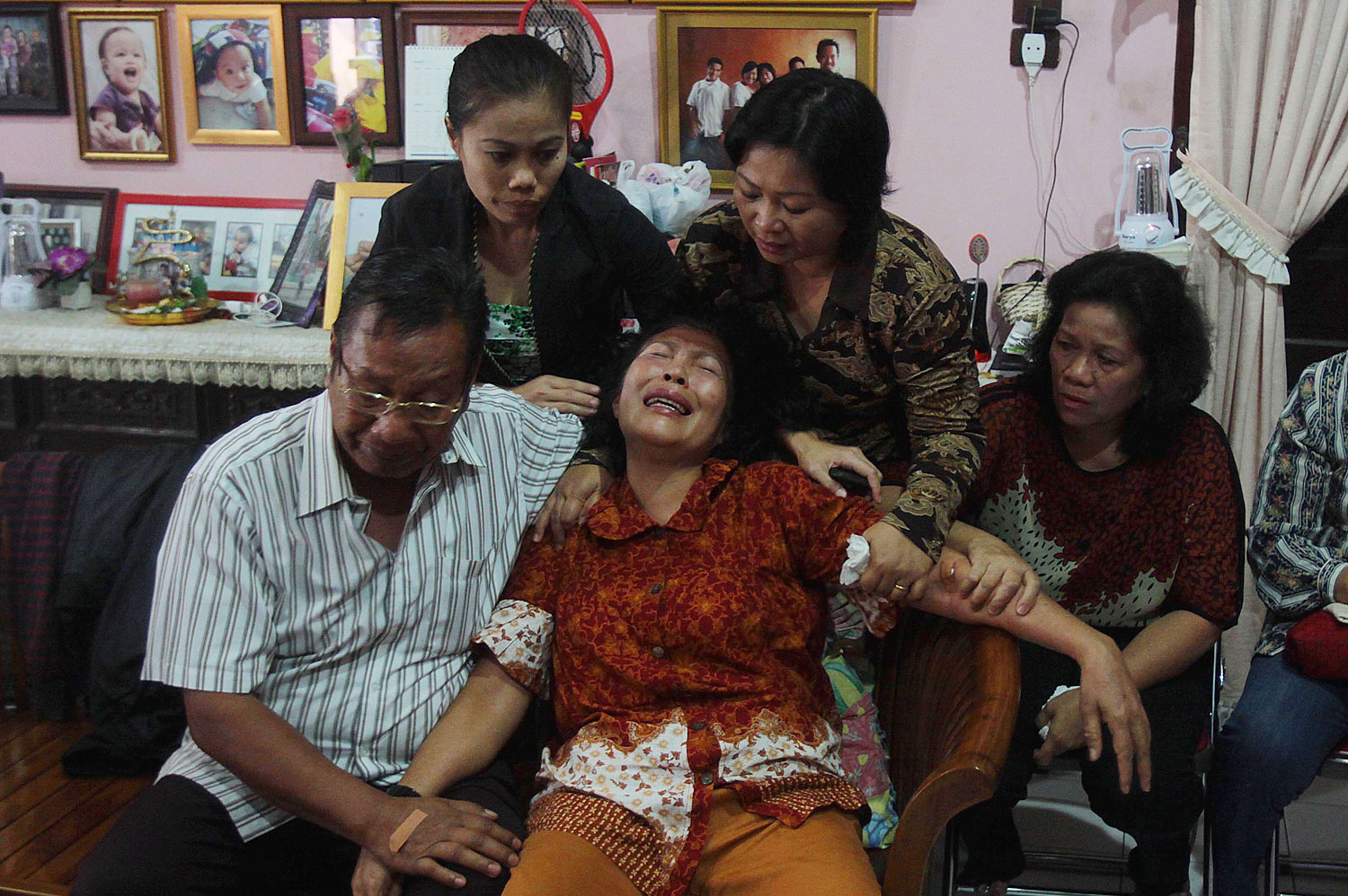 Risman Siregar, left, comforts his wife Erlina Panjaitan, center — both are parents of Firman Chandra Siregar, a 24-year-old Indonesian passenger of Malaysia Airlines Flight 370 — on March 9, 2014, in Medan, Indonesia