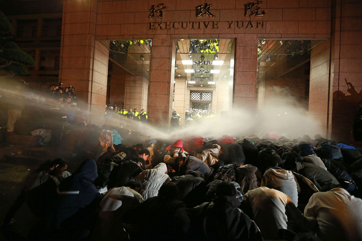 Protesters are sprayed with a water cannon during a demonstration outside the Executive Yuan in Taipei early on March 24, 2014, following Taiwan President Ma Ying-jeou's refusal to scrap a contentious trade agreement with China.