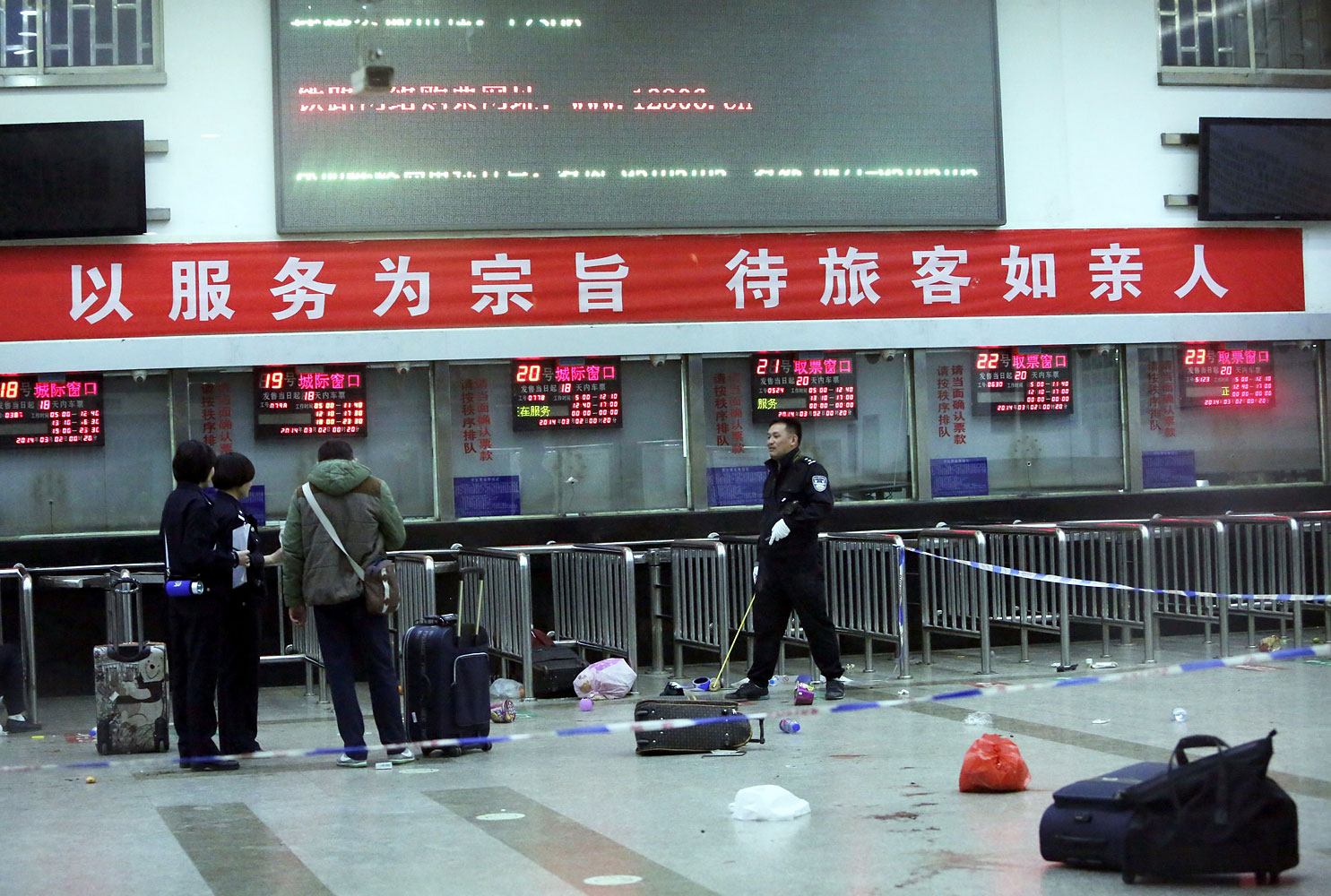 Chinese police investigators inspect the scene of an attack at the railway station in Kunming, southwest China's Yunnan province, on March 2, 2014