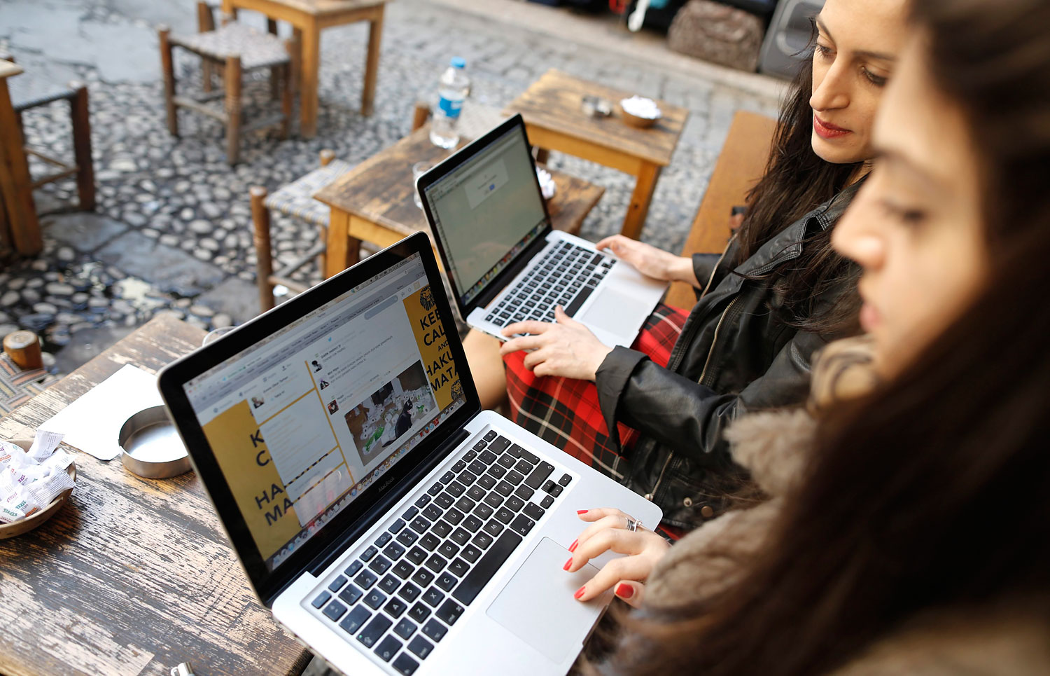 Two Turkish women try to get on Twitter website on their laptops at a cafe in Istanbul, March 21, 2014.