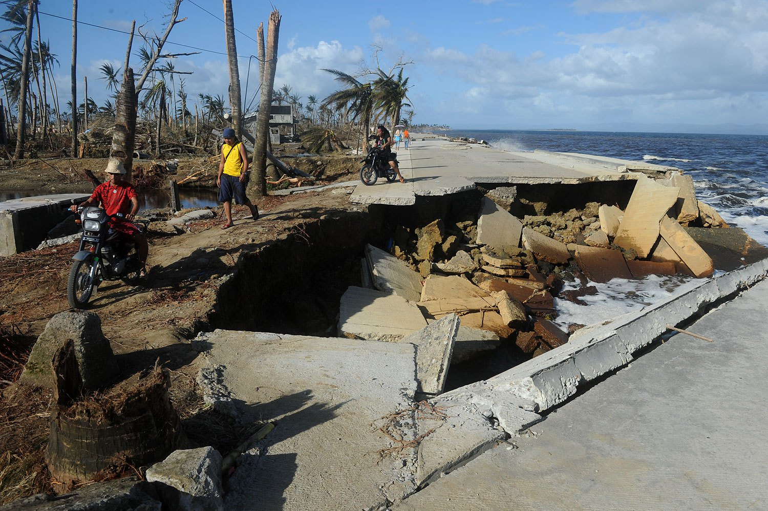 A motorist crosses a collapsed highway caused by the storm surge in Palo, in Leyte province, on Nov. 10, 2013