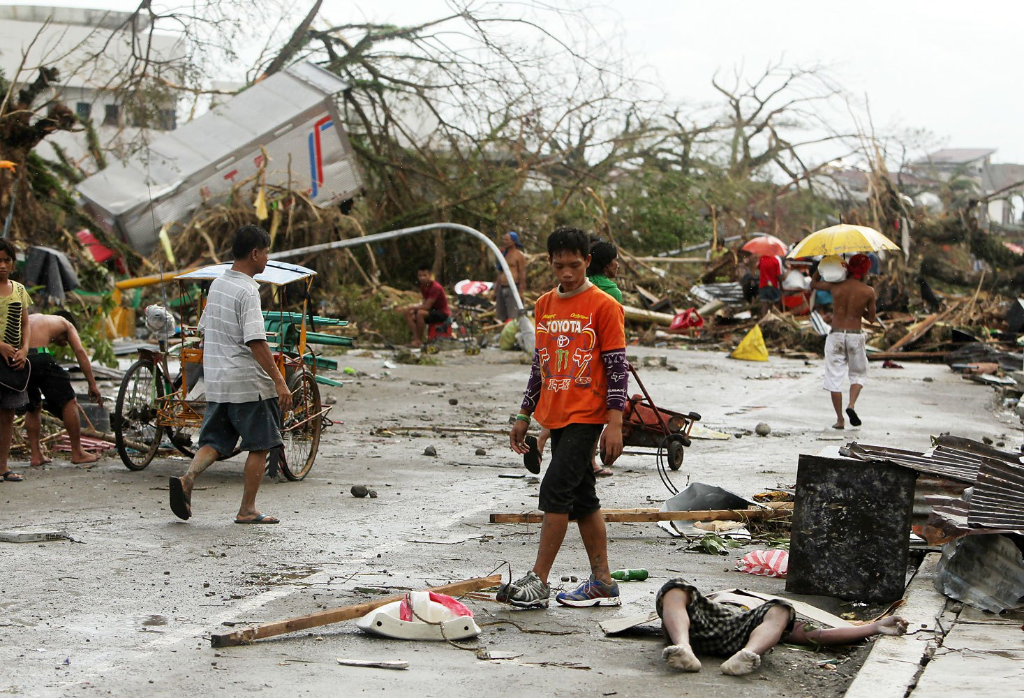 Filipinos walk past a victim left on the side of a street in the typhoon-devastated city of Tacloban, in the Philippines' Leyte province, on Nov. 9, 2013