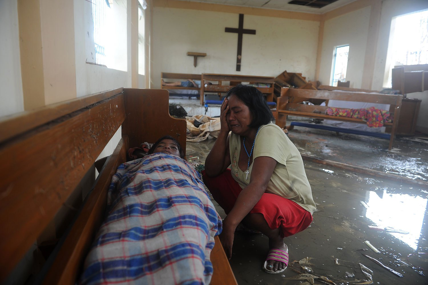 A mother weeps beside her dead son at a chapel in the aftermath of Supertyphoon Haiyan in Tacloban, in Leyte province, Nov. 9, 2013