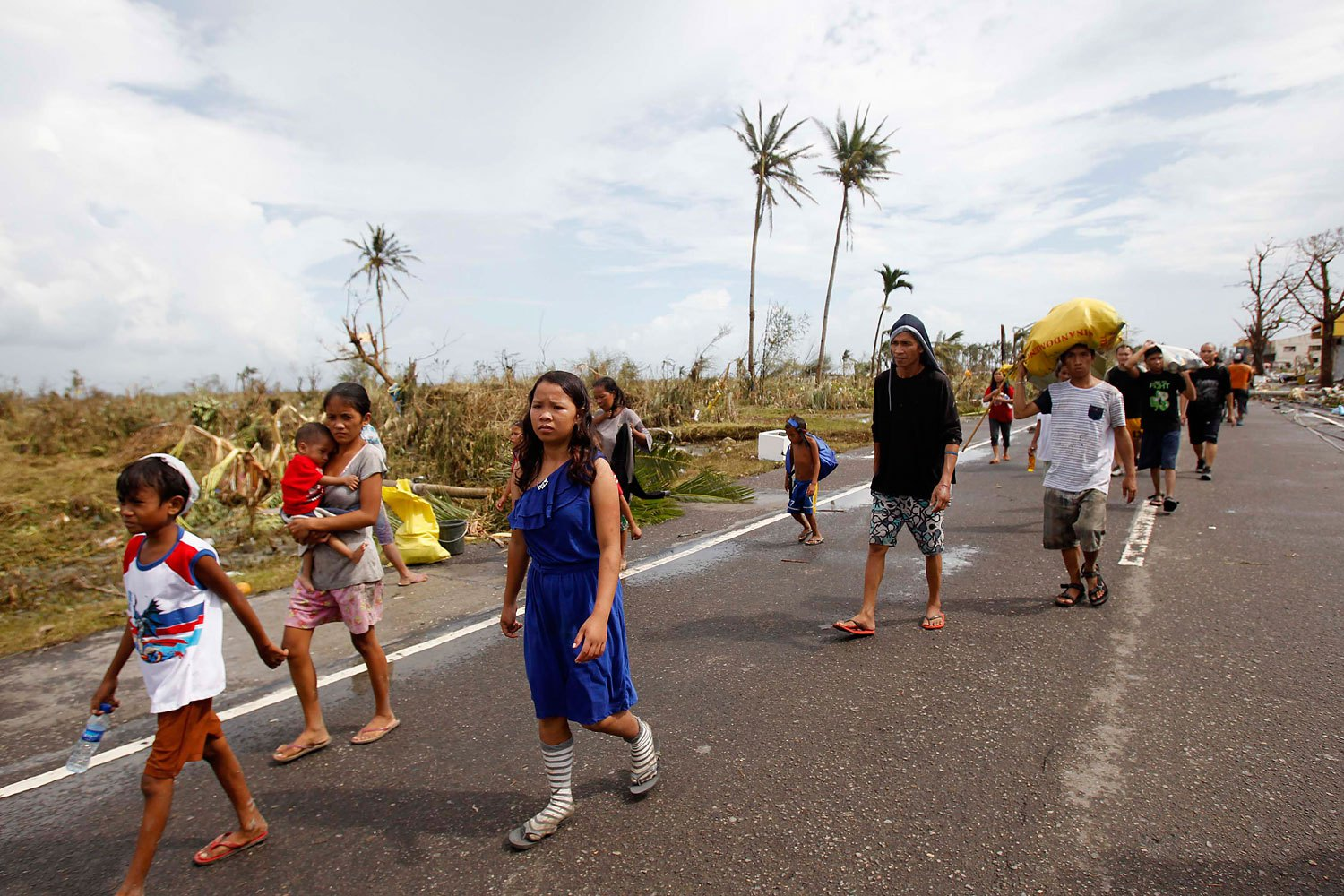 Survivors walk past a damaged town on Nov. 9, 2013, after strong winds brought by Supertyphoon Haiyan battered Tacloban, in central Philippines