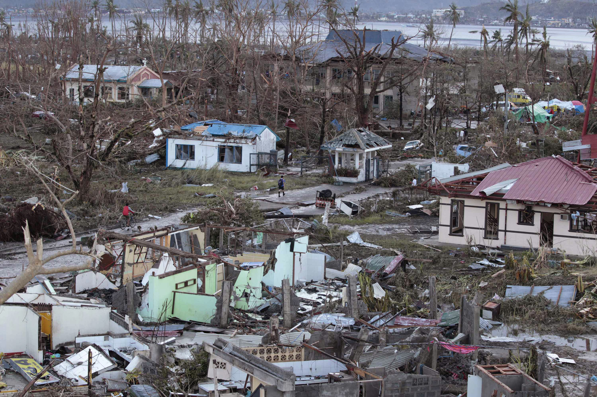 A resident walks by remains of houses on Nov. 9, 2013, after Supertyphoon Haiyan slammed into Tacloban, in the Philippines' Leyte province