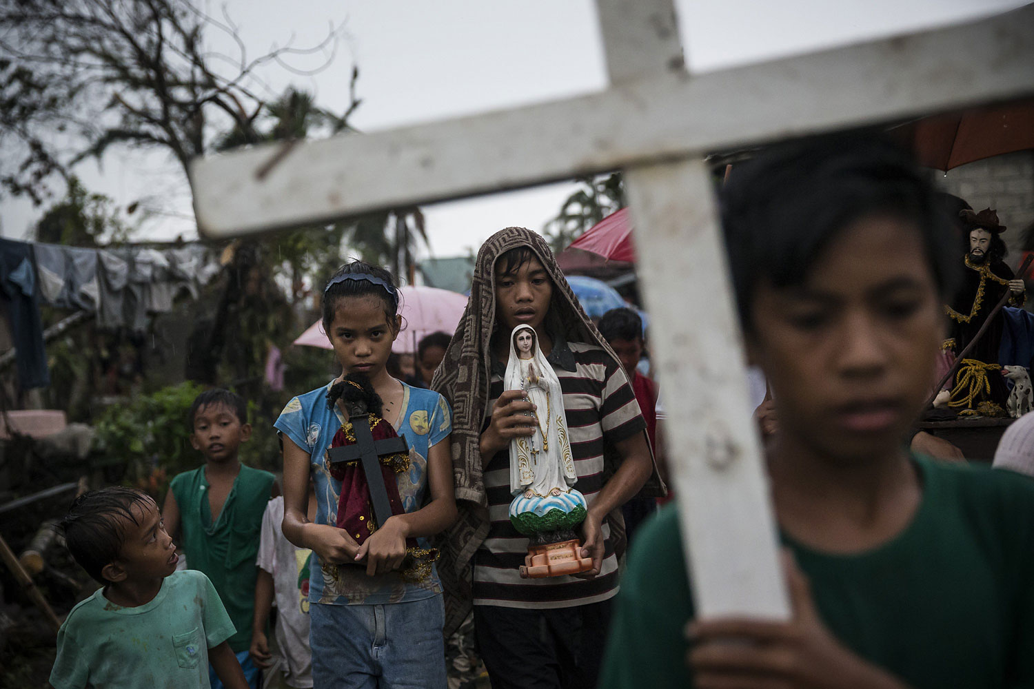 Villagers carry religious statues during a procession before taking part in a Latin mass ceremony at a local Chapel in Santa Rita township on November 22, 2013 in Eastern Samar, Philippines.