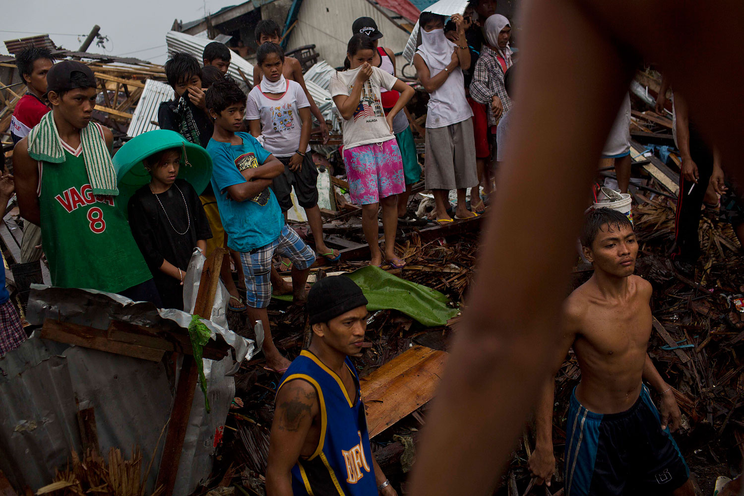Typhoon Haiyan survivors stand in the rain and watch as people from their destroyed neighborhood search for dead bodies in the rubble in Tacloban, Philippines on November 22, 2013.