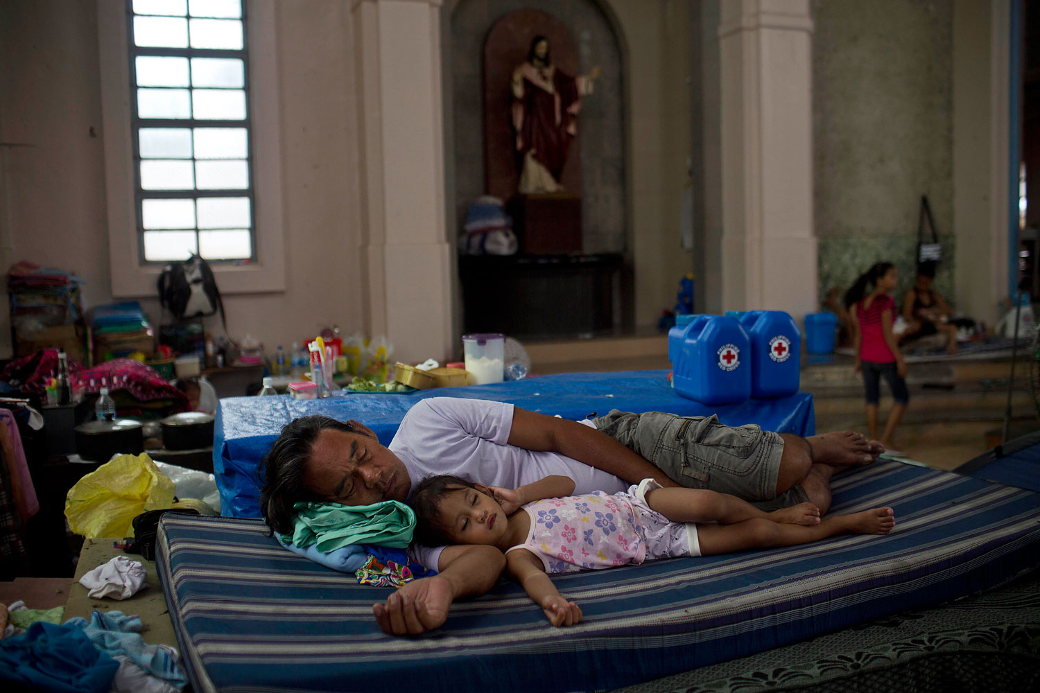 A man and his child sleep inside a Catholic Cathedral where they and other Typhoon Haiyan survivors are taking shelter in Tacloban, Philippines on November 22, 2013.