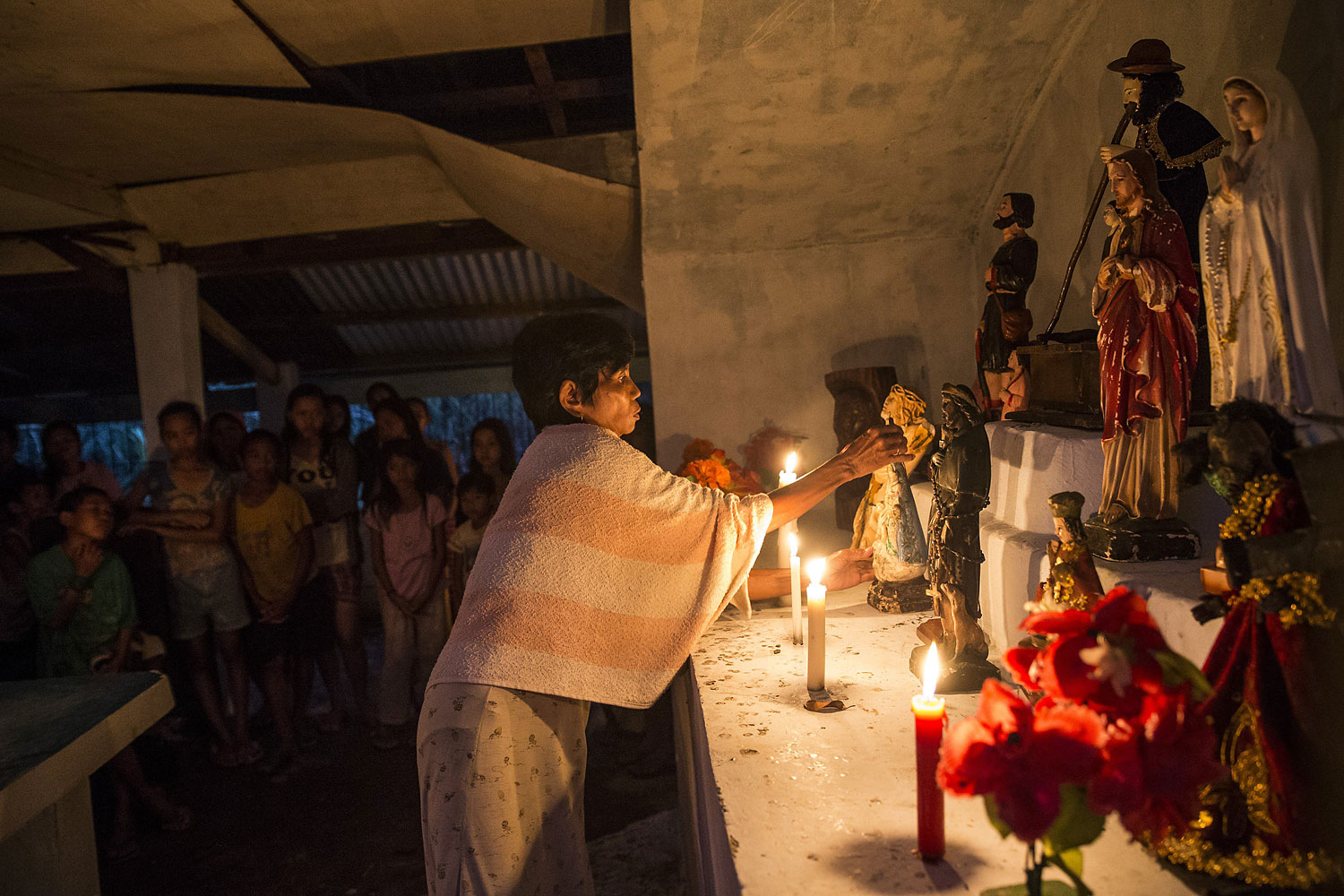 A woman arranges religious statues during a Latin mass ceremony at a local Chapel in Santa Rita township on November 22, 2013 in Eastern Samar, Philippines.