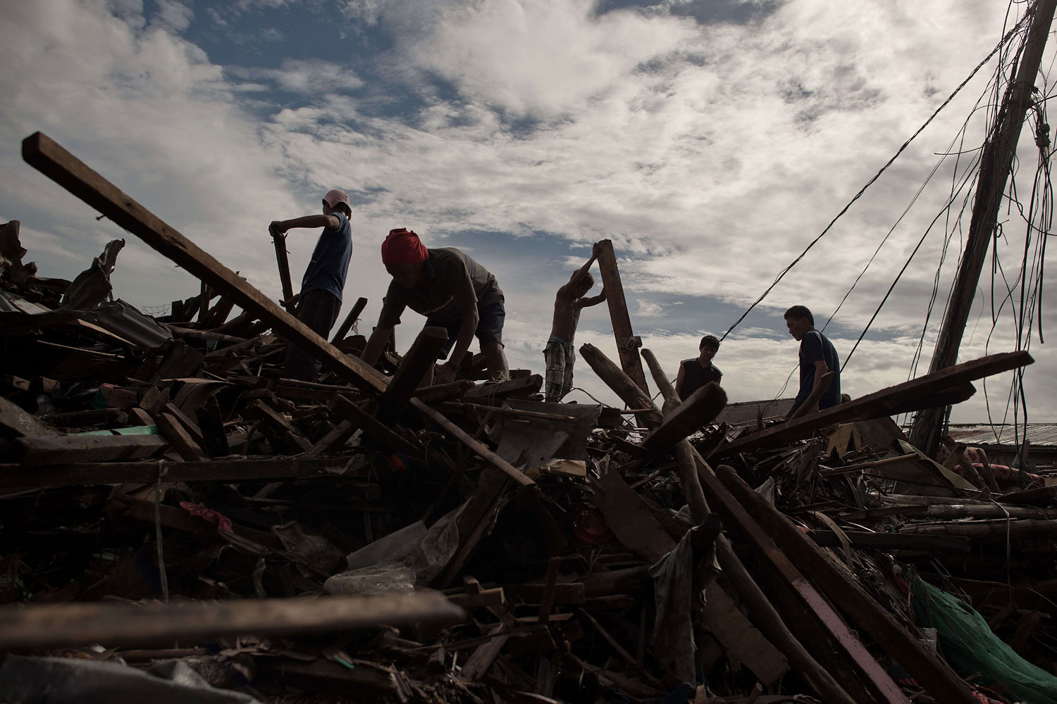 Residents work to clear debris left in the aftermath by Super Typhoon Haiyan in the Philippine city of Tacloban on November 21, 2013.