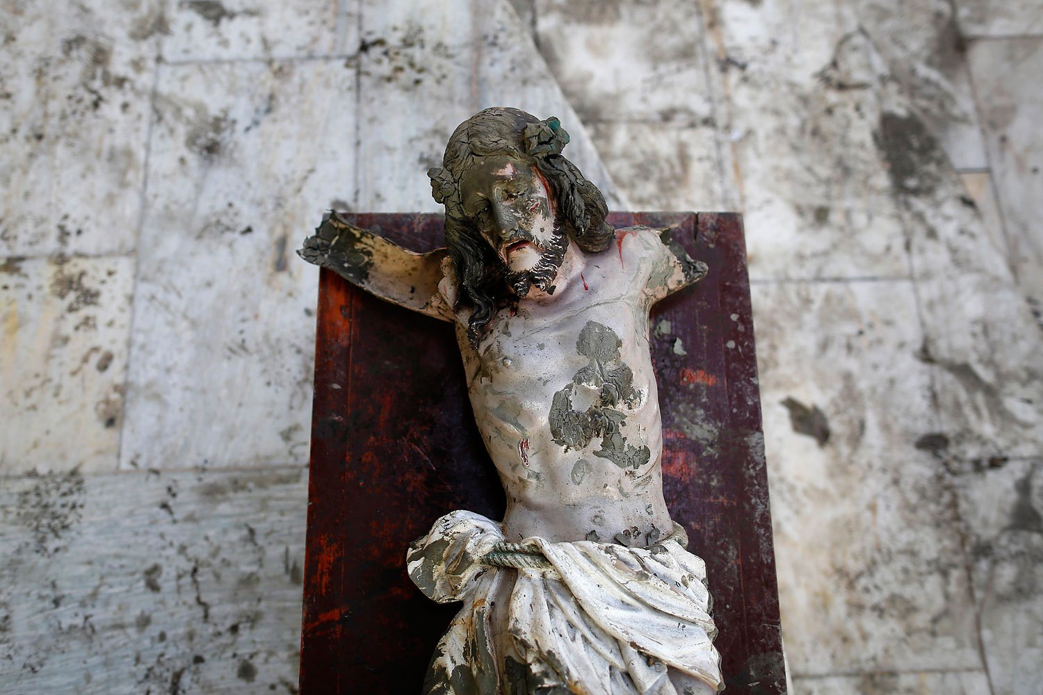A damaged statue of Jesus Christ that was recovered from rubbles is placed in a church in an area wrecked by Typhoon Haiyan in Tacloban November 21, 2013.