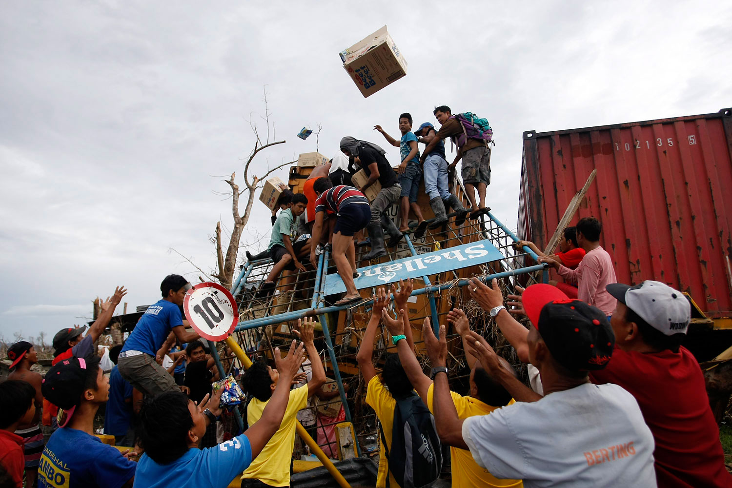 Filipino villagers force open a washed up container containing grocery items in the super typhoon devastated city of Tacloban, Leyte island province, Philippines, November 20, 2013.