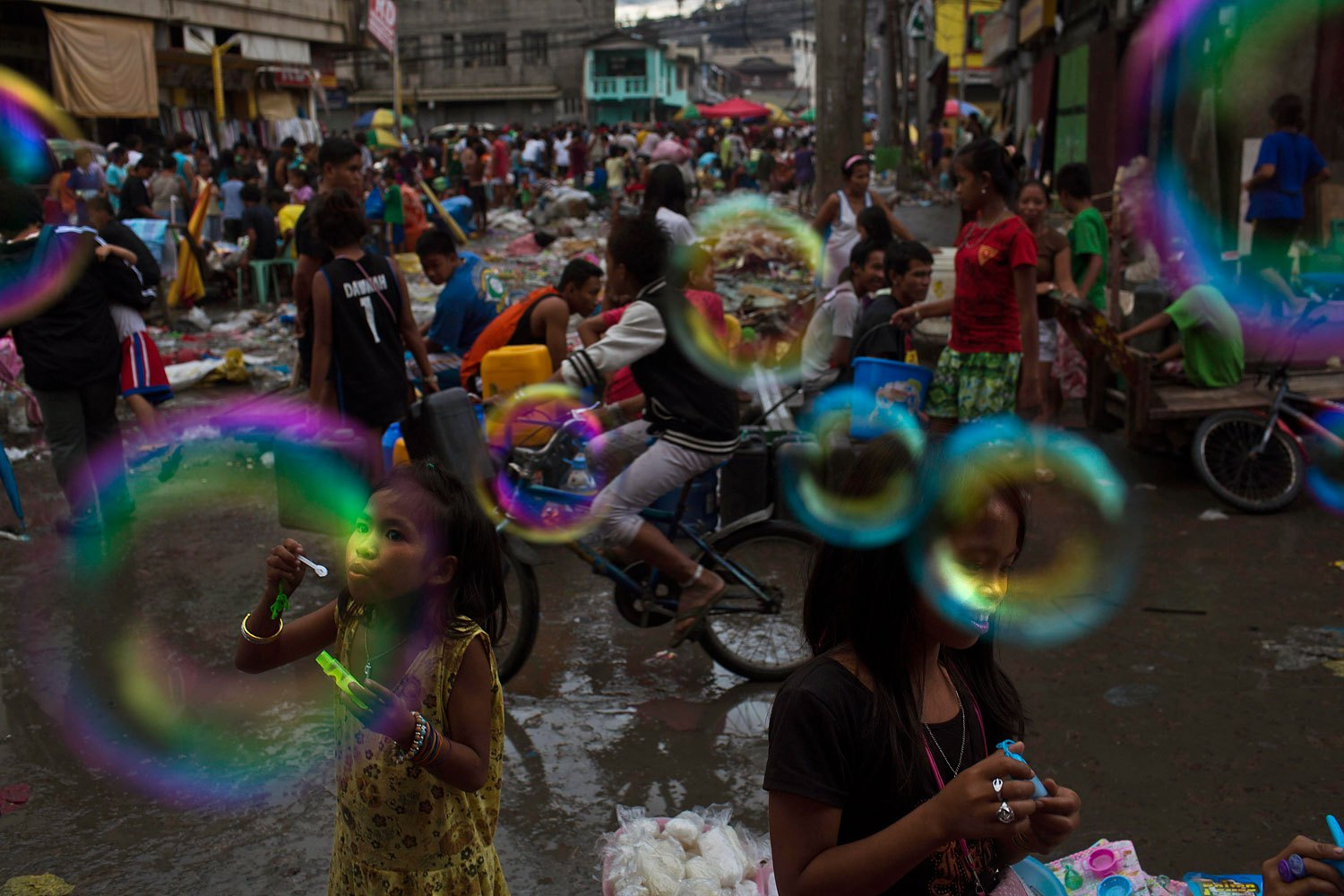 Children who survived Typhoon Haiyan blow bubbles in the destroyed market of Tacloban, Philippines, November 20, 2013.