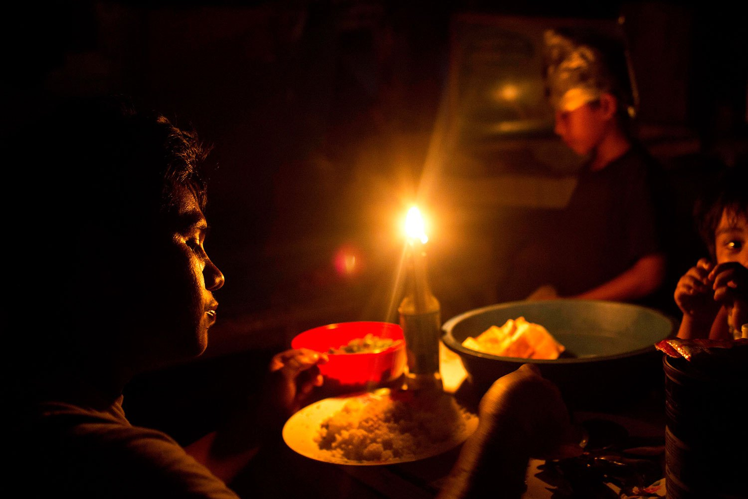 A Typhoon Haiyan survivor and his sons eat dinner by candlelight inside a destroyed and abandoned vegetable market now used as a shelter in Tacloban, Philippines, November 20, 2013.