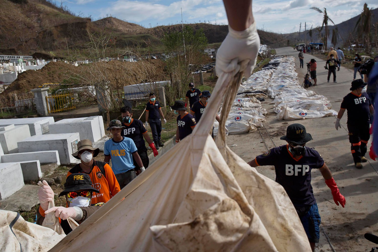 Filipino firemen unload Typhoon Haiyan victims in body bags from a truck on the roadside until forensic experts can register and bury them in a mass grave outside of Tacloban, Philippines on November 19, 2013.