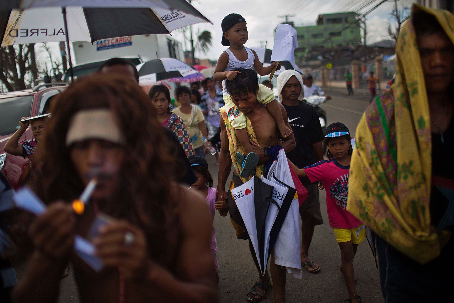 People march in the rain Tacloban, Philippines during a procession to call for courage and resilience among their Typhoon Haiyan survivors on November 19, 2013.