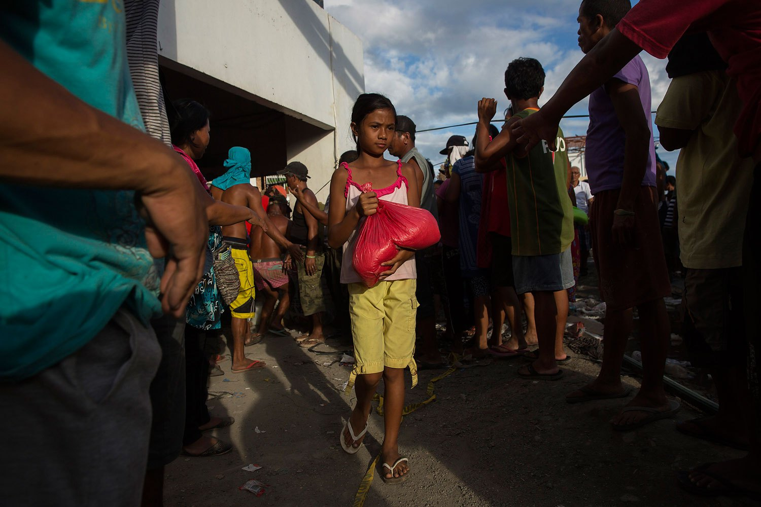A girl affected by Typhoon Haiyan collects food aid in Tanauan, Philippines on November 19, 2013.