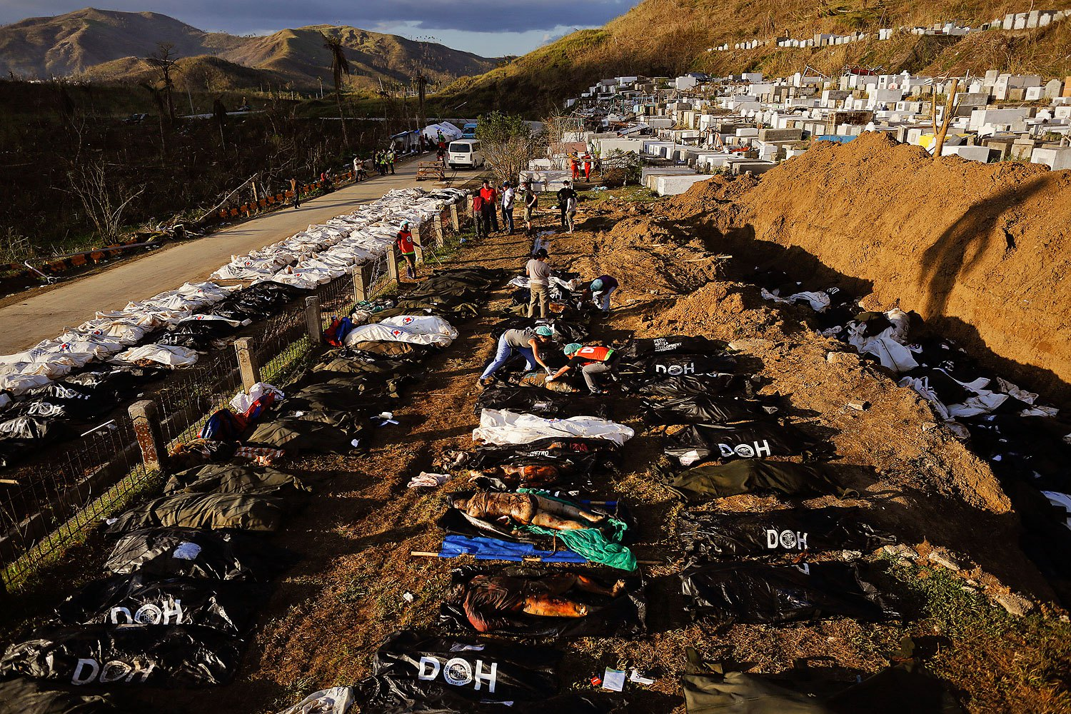 Forensic experts work on a mass grave with more than 700 bodies of victims of Typhoon Haiyan just outside Tacloban on November 18, 2013.