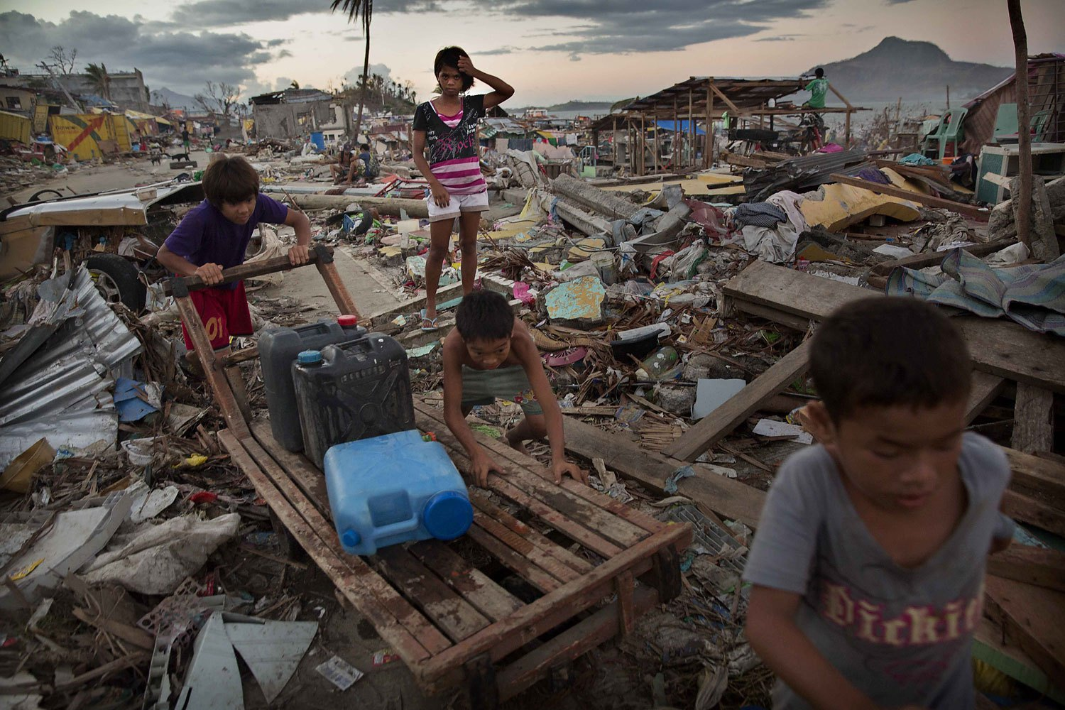 Young residents push a cart as they collect water in an area destroyed in the aftermath of Typhoon Haiyan on November 18, 2013 in Tacloban, Philippines.
