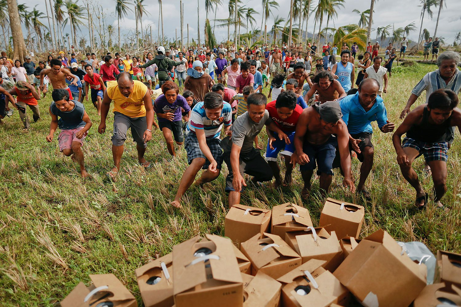 Survivors of Typhoon Haiyan rush to grab fresh water delivered by a U.S. military helicopter to their isolated village north of Tacloban, November 17, 2013.