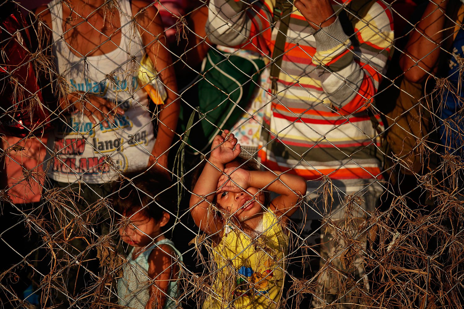 People who trying to leave the devastated town look through the fence of Tacloban airport, which remains a point of exodus for survivors of typhoon Haiyan, November 17, 2013.