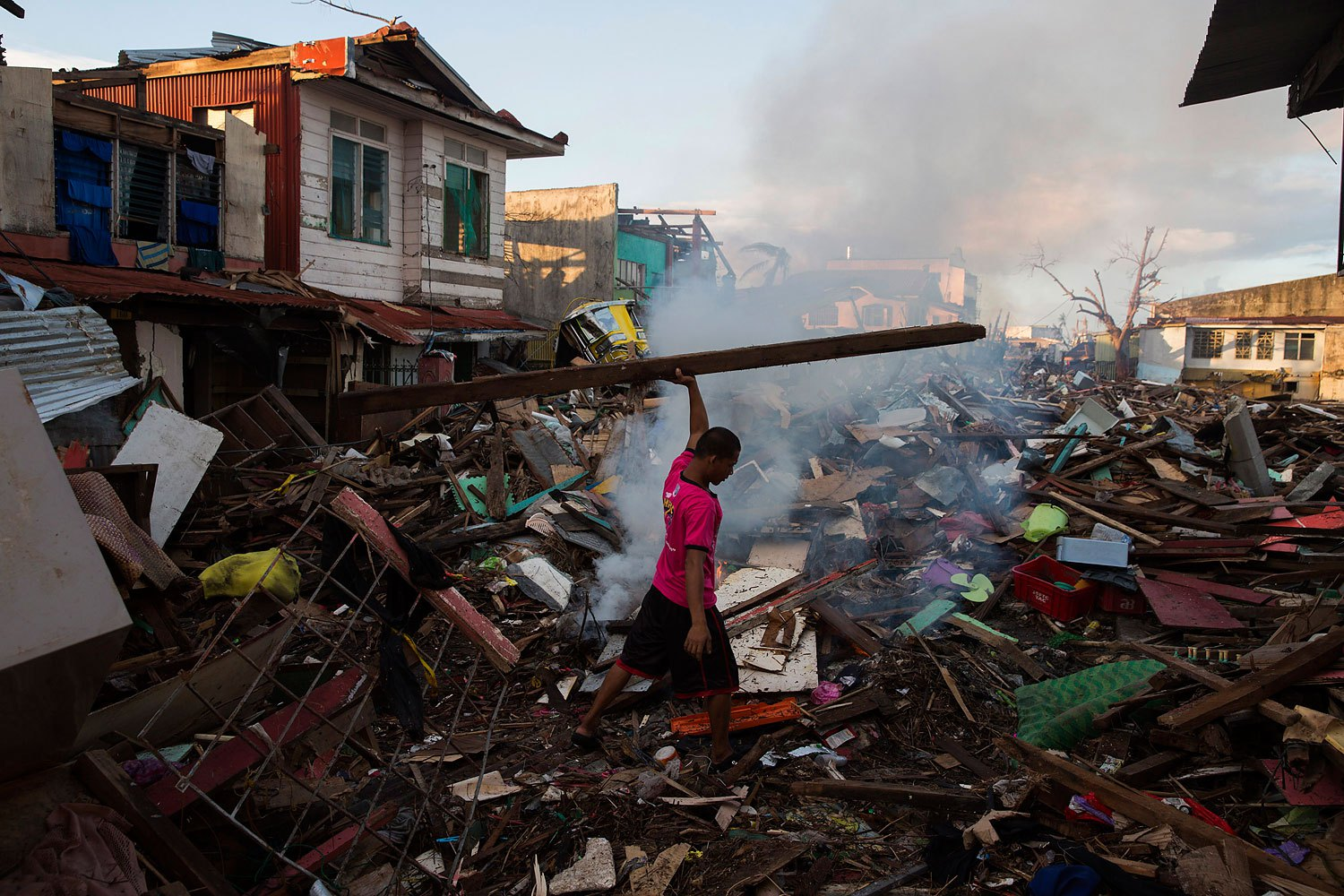 A man salvages wood in a neighbourhood destroyed by Typhoon Haiyan in Tacloban, Philippines on November 17, 2013.