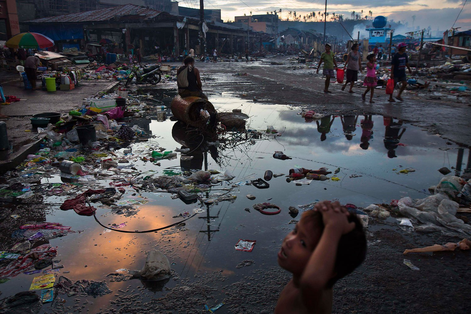 Typhoon Haiyan survivors walk through the ruins in the streets of Tacloban, Philippines, November 17, 2013.